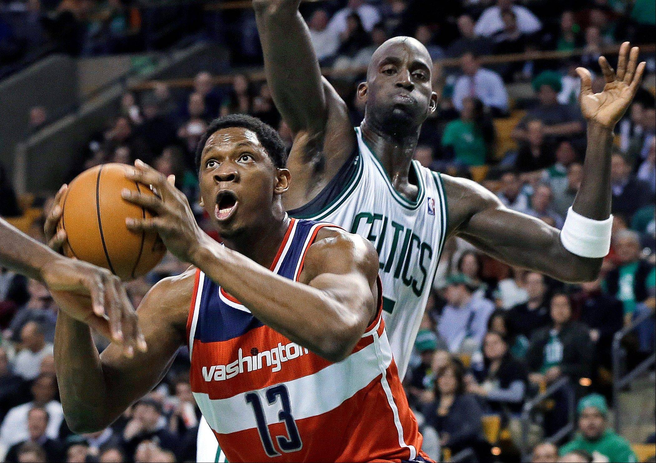 Washington Wizards forward Kevin Seraphin (13) drives to the basket past Boston Celtics forward Kevin Garnett Wednesday during the first half in Boston.