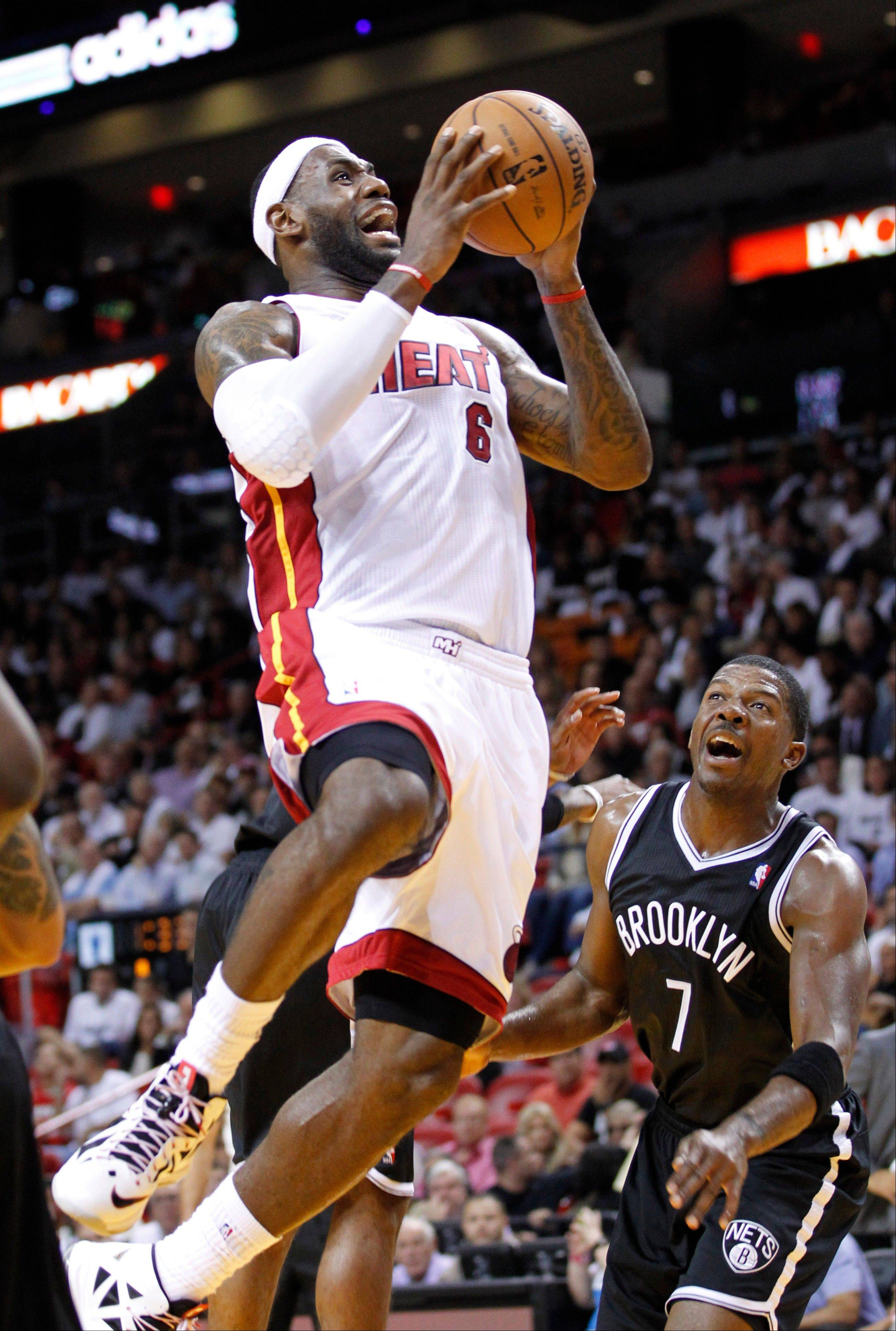 Miami Heat forward LeBron James goes up for a shot against Brooklyn Nets guard Joe Johnson Wednesday during the first half in Miami.