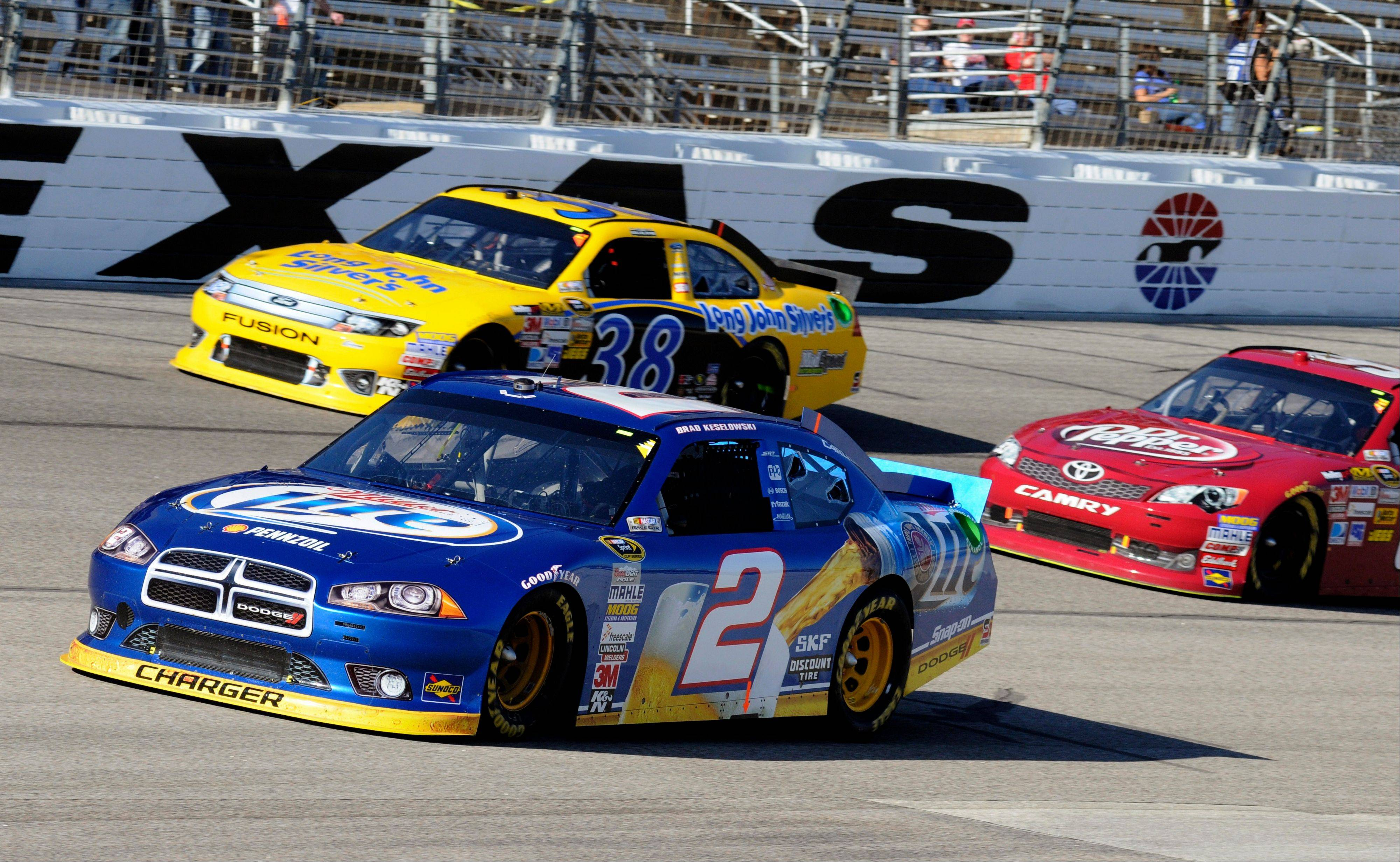 Brad Keselowski (2) comes out of Turn 4 in front of David Gilliland (38) and Travis Kvapil, right, Sunday during the NASCAR Sprint Cup Series race in Fort Worth, Texas.