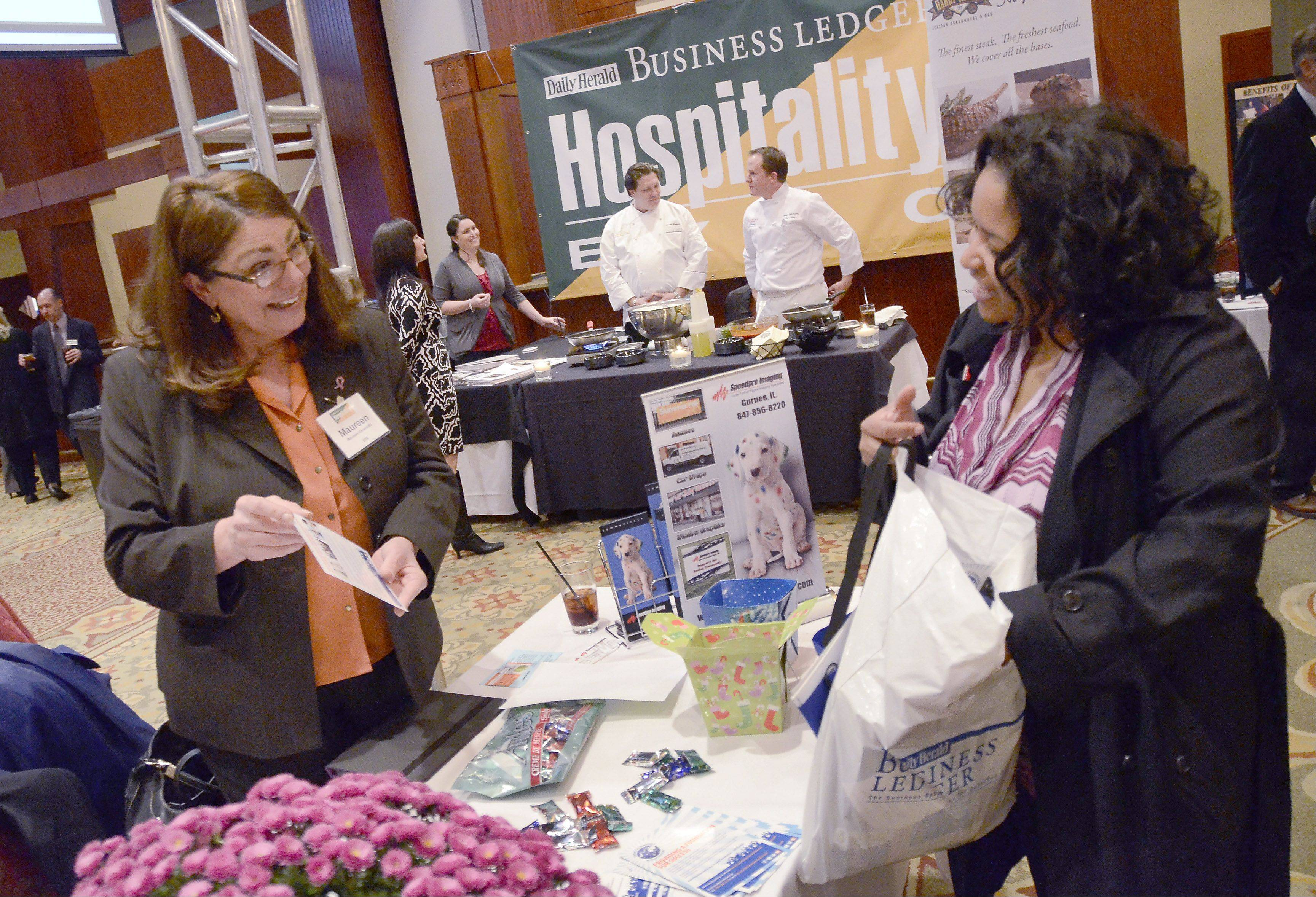 Bill Zars/bzars@dailyherald.com Maureen Kmieciak, left, with Speedpro Imaging of Gurnee and event coordinator Rashaan Tobin with Events of Radiance chat at the Daily Herald Business Ledger Northwest Hospitality Expo at the Meadows Club in Rolling Meadows.