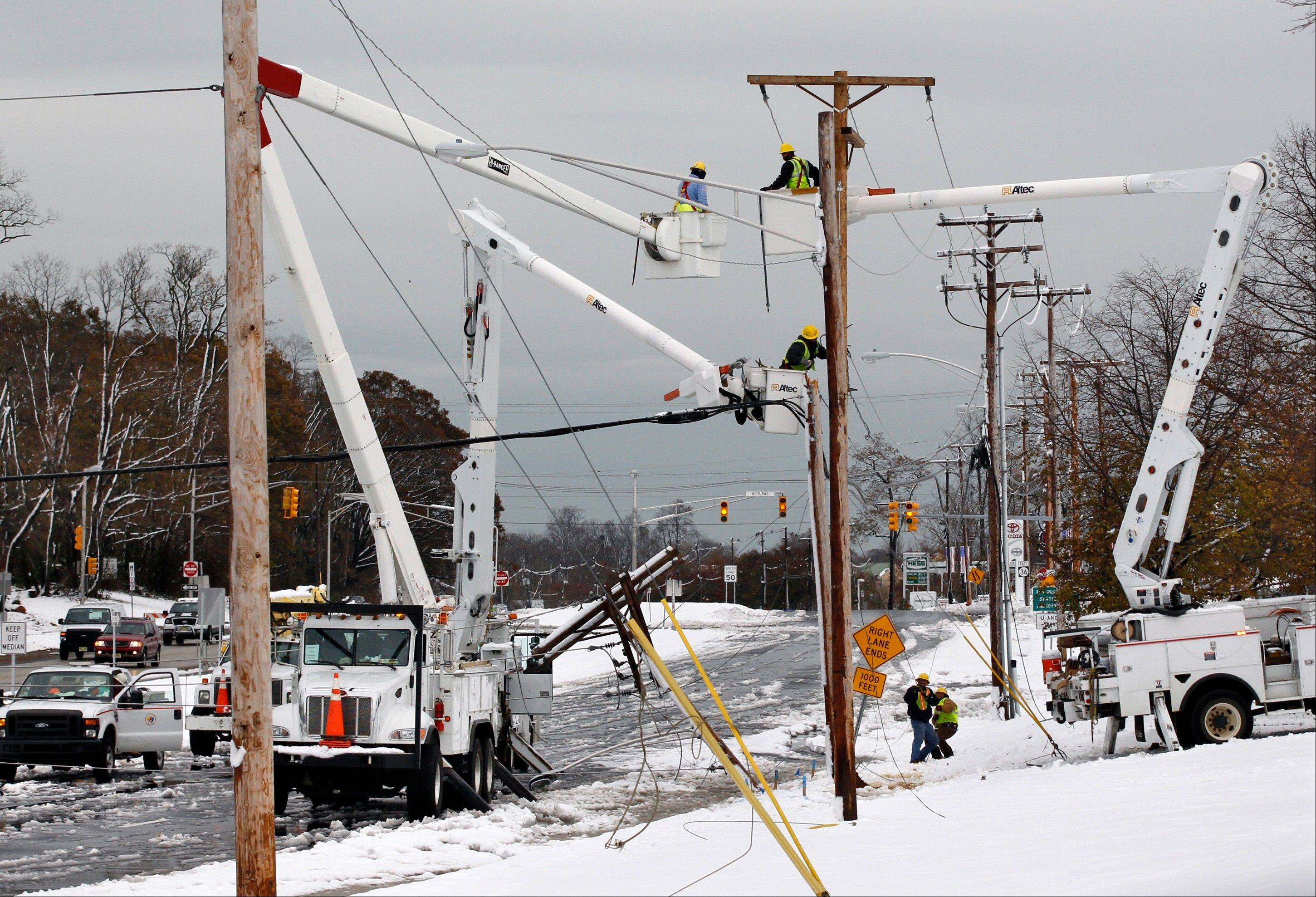 Crews work to repair downed wires Thursday in Eatontown, N.J., after a nor�easter brought high winds and dumped as much as a foot of snow overnight in the region pounded by Superstorm Sandy last week.