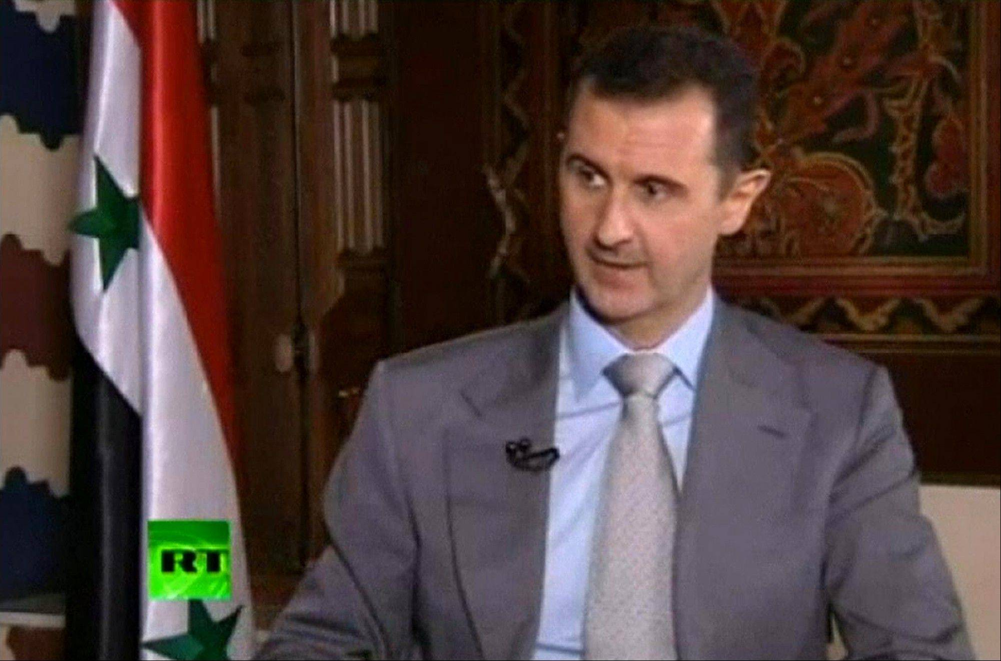 In this image made from video, Syrian President Bashar Assad speaks with English-language television channel Russia Today recorded at an unknown date in Damascus, Syria.