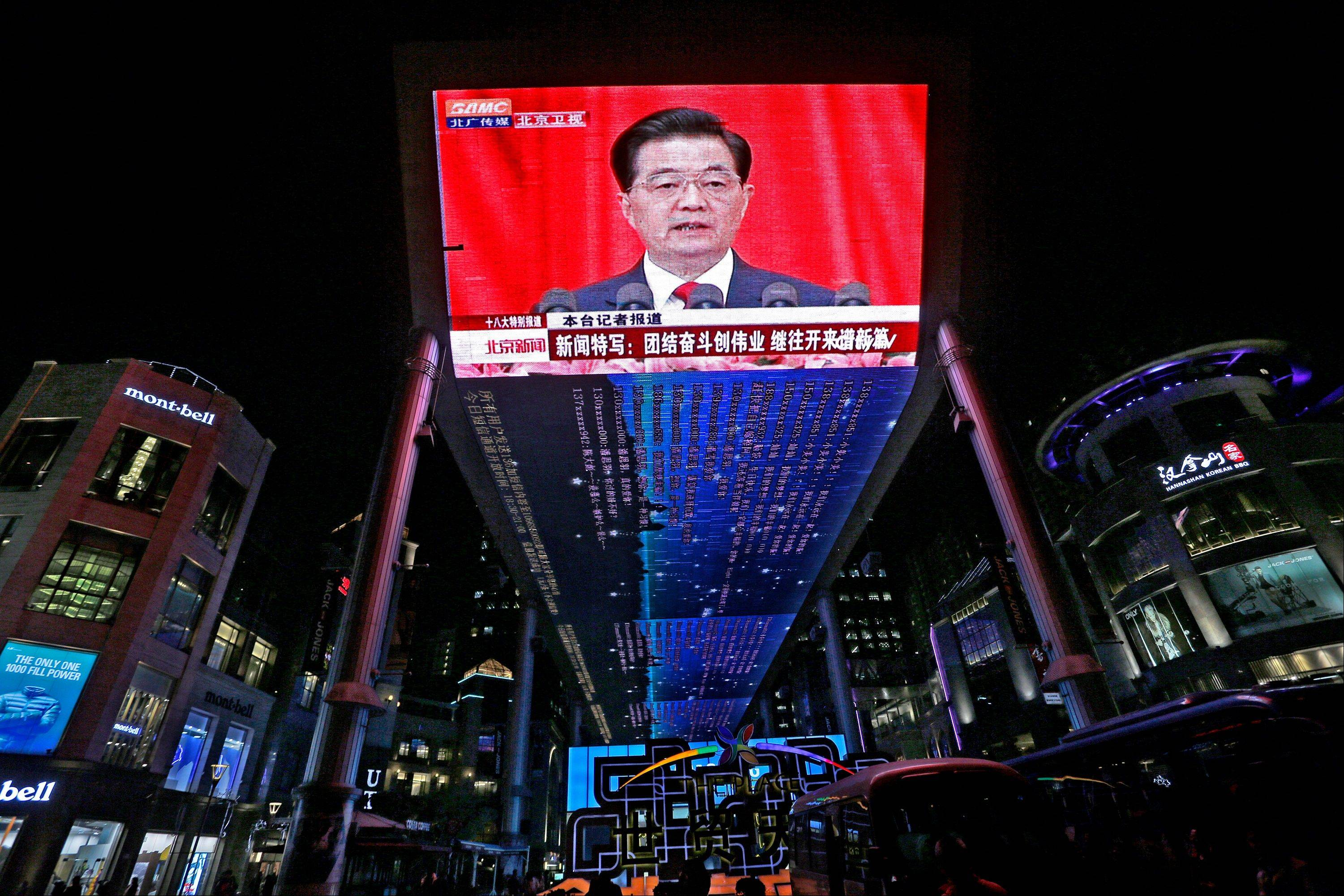 A huge screen shows a broadcast of Chinese President Hu Jintao speaking Thursday at the opening session of the 18th Communist Party Congress at the Great Hall of the People in Beijing.