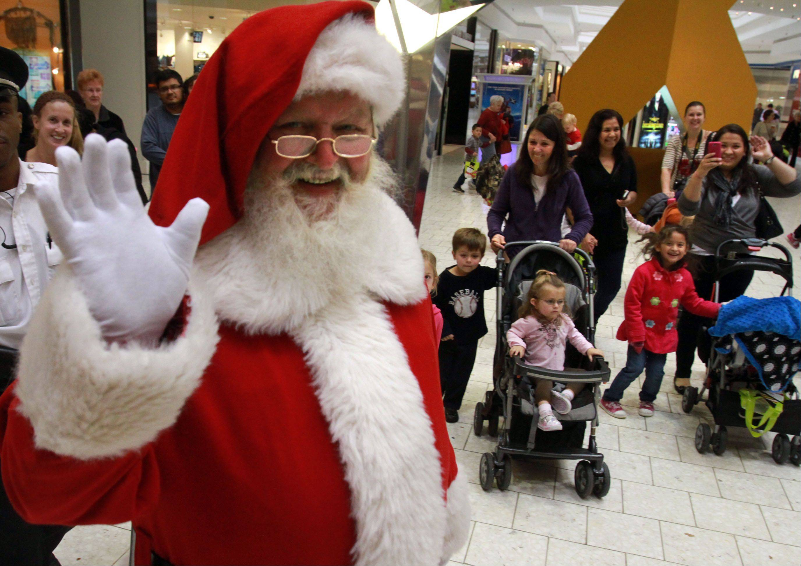 Santa Claus leads a parade up and down the wings of Woodfield Mall in Schaumburg after his arrival Thursday to kick off the holiday shopping season.