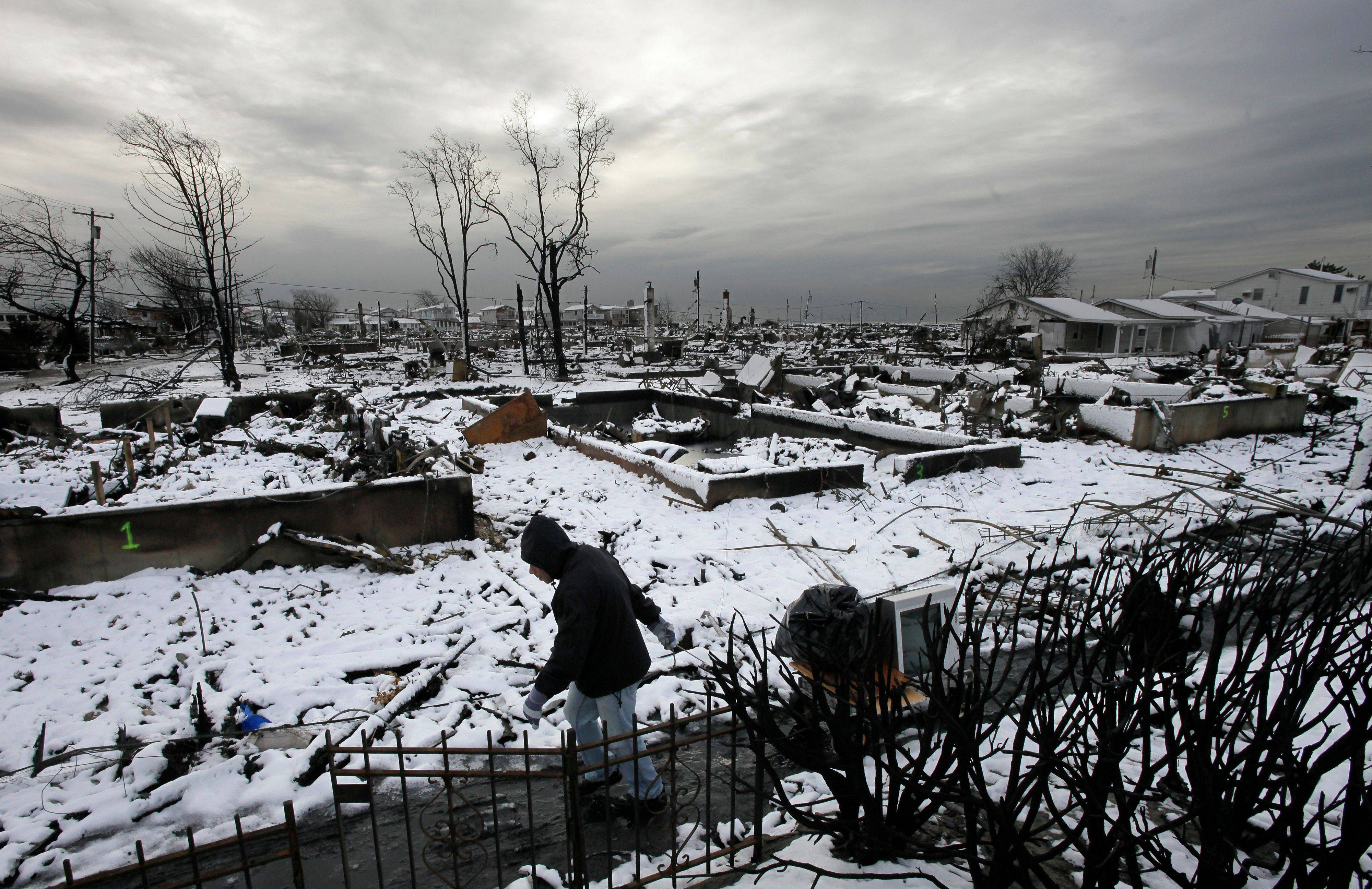 Damon Rasinya carts debris from his family home past the fire-scorched landscape of Breezy Point after a Nor�easter snow, Thursday, Nov. 8, 2012 in New York. The beachfront neighborhood was devastated during Superstorm Sandy when a fire pushed by the raging winds destroyed many homes.