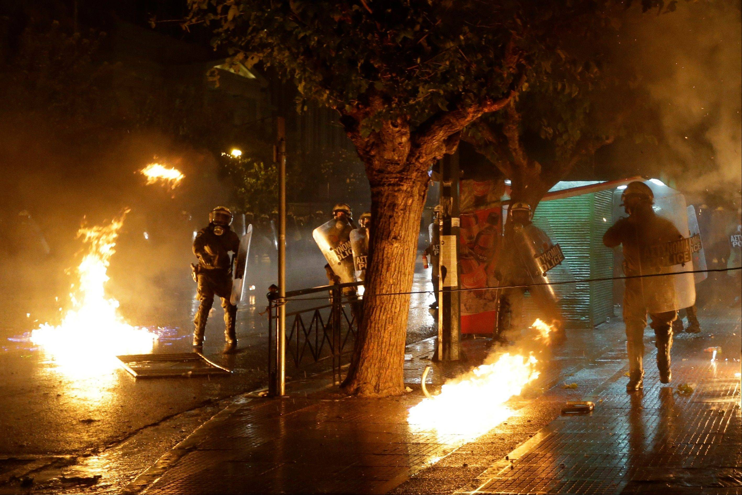 Petrol bombs thrown by protesters explode near riot police in front of the parliament during clashes in Athens, Wednesday Nov. 7, 2012. Greeceís fragile coalition government faces its toughest test so far when lawmakers vote later Wednesday on new painful austerity measures demanded to keep the country afloat, on the second day of a nationwide general strike. The 13.5 billion euro ($17.3 billion) package is expected to scrape through Parliament, following a hasty one-day debate.