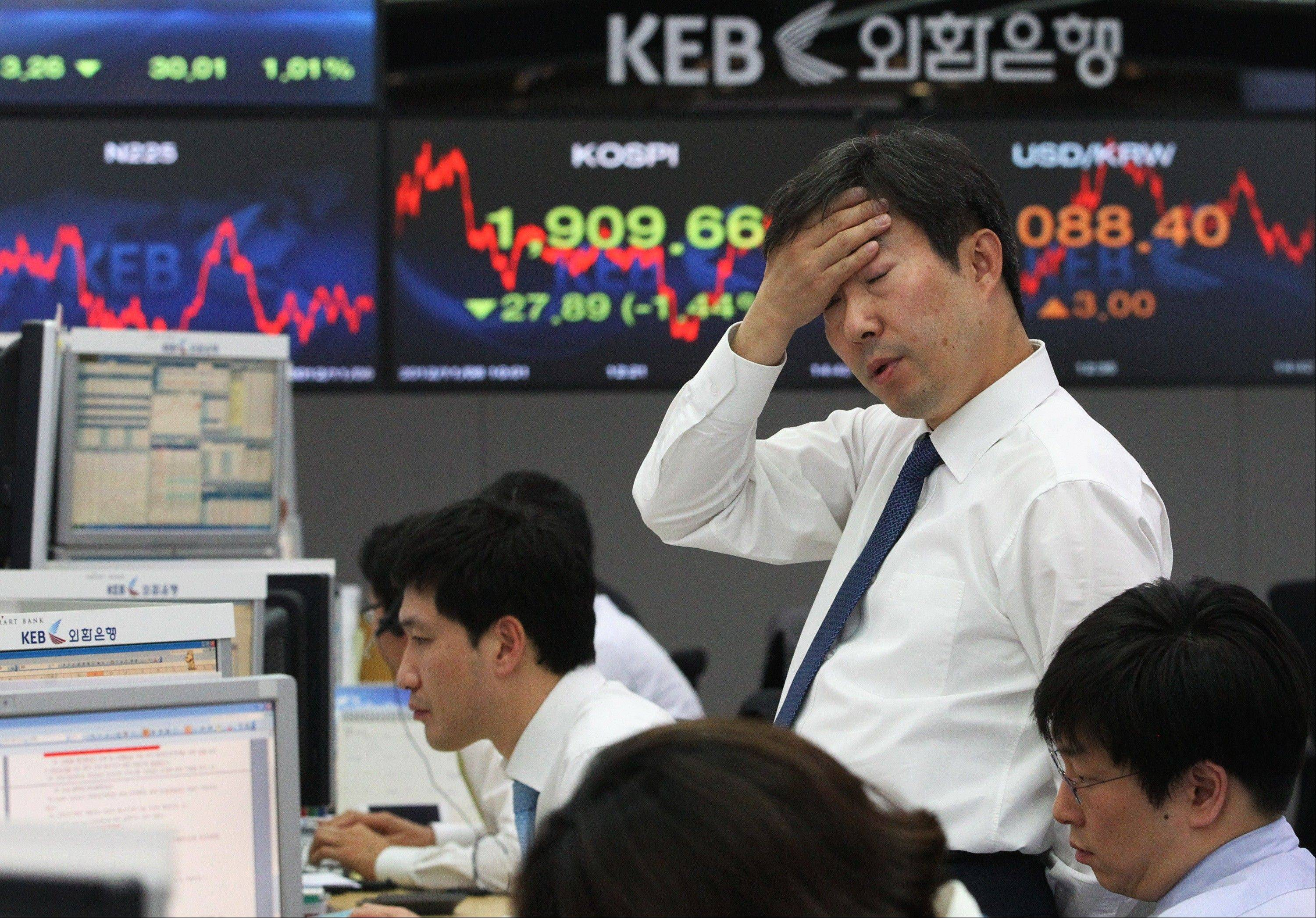 A currency trader reacts in front of screens showing the Korea Composite Stock Price Index (KOSPI), center, and foreign exchange rate, right, at the foreign exchange dealing room of the Korea Exchange Bank headquarters in Seoul, South Korea, Thursday, Nov. 8, 2012. South Korea's Kospi dropped 1.19 percent at 1,914.43.