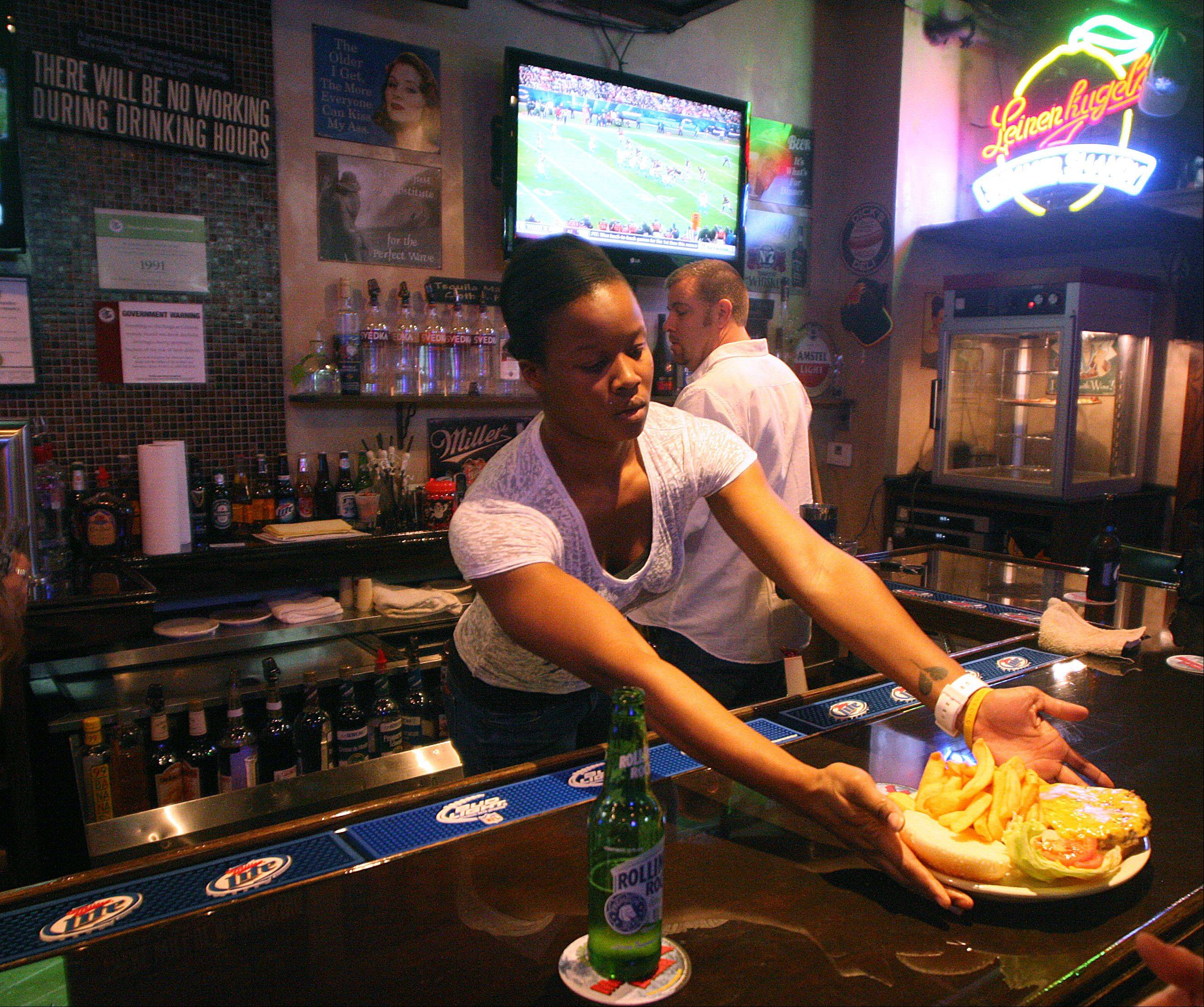 Manager Essence Ashford serves a burger and fries at the Pour House Bar & Grill in East Dundee.