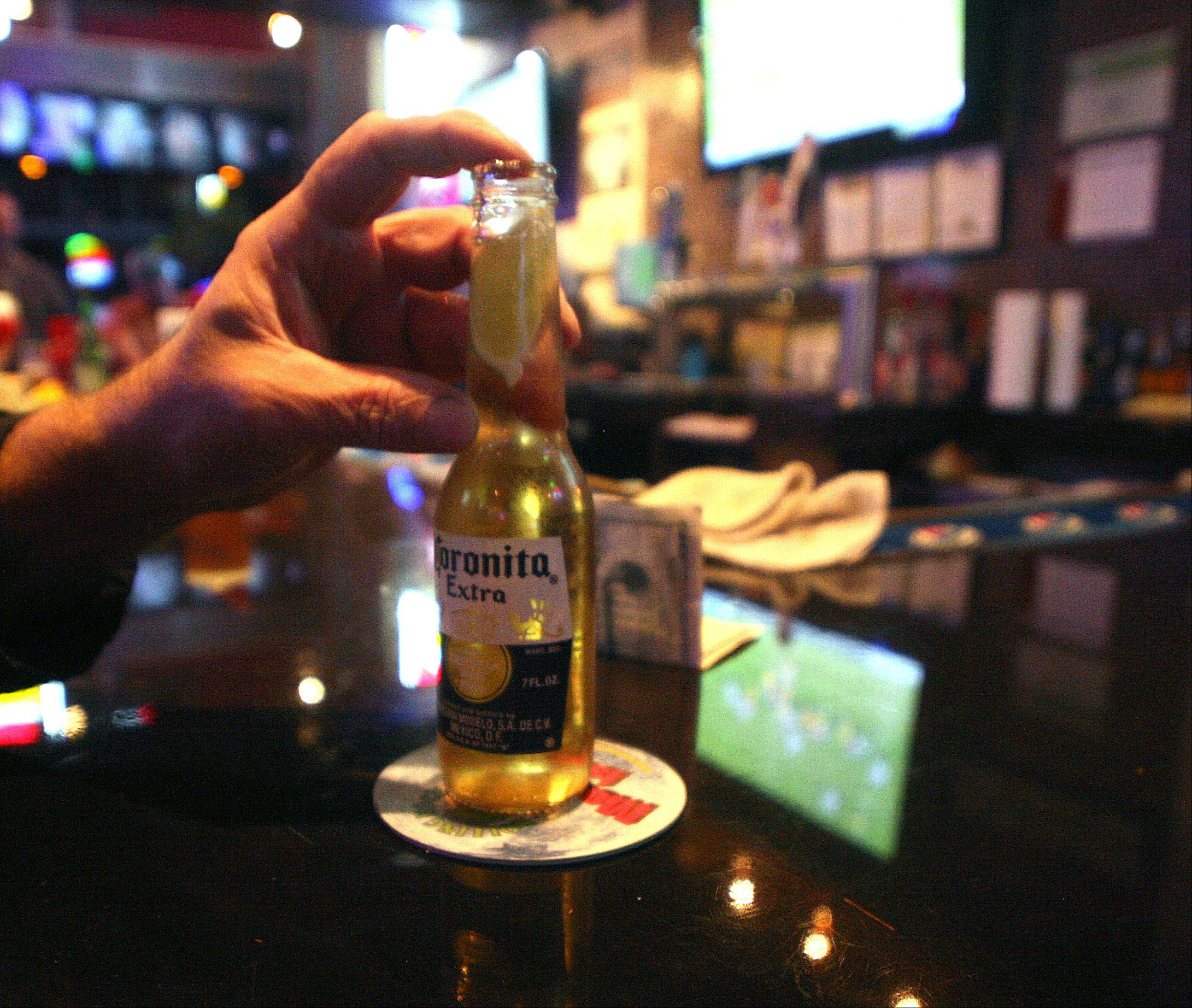 Joel Tarpinian of Island Lake puts the finishing touch on a lime in his beer at the Pour House Bar & Grill.