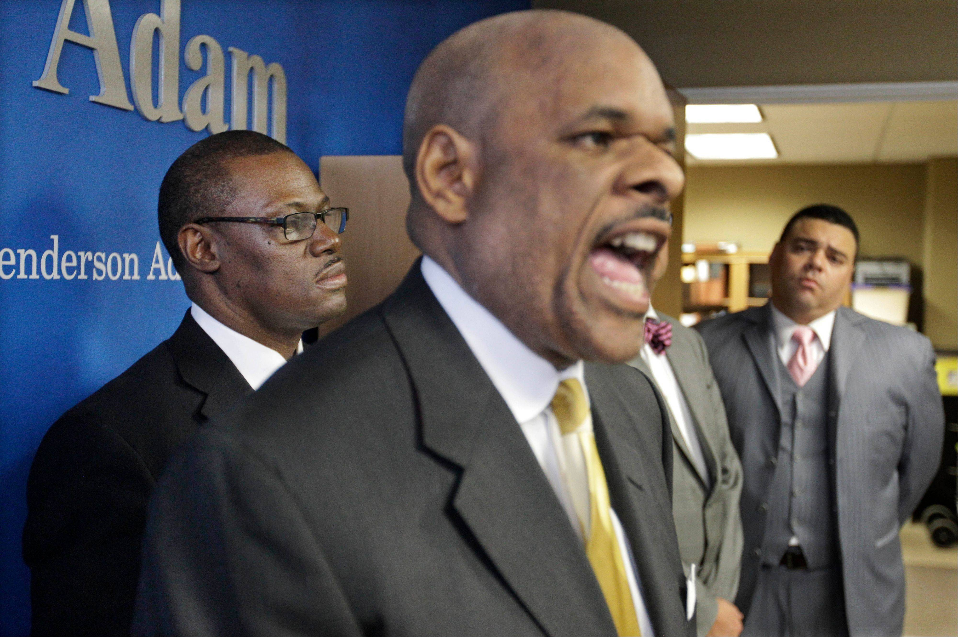 Victor Henderson, attorney for Democrat Derrick Smith, left, speaks during a news conference with his client and fellow lawyer Sam Adam Jr., right, on Thursday in Chicago.