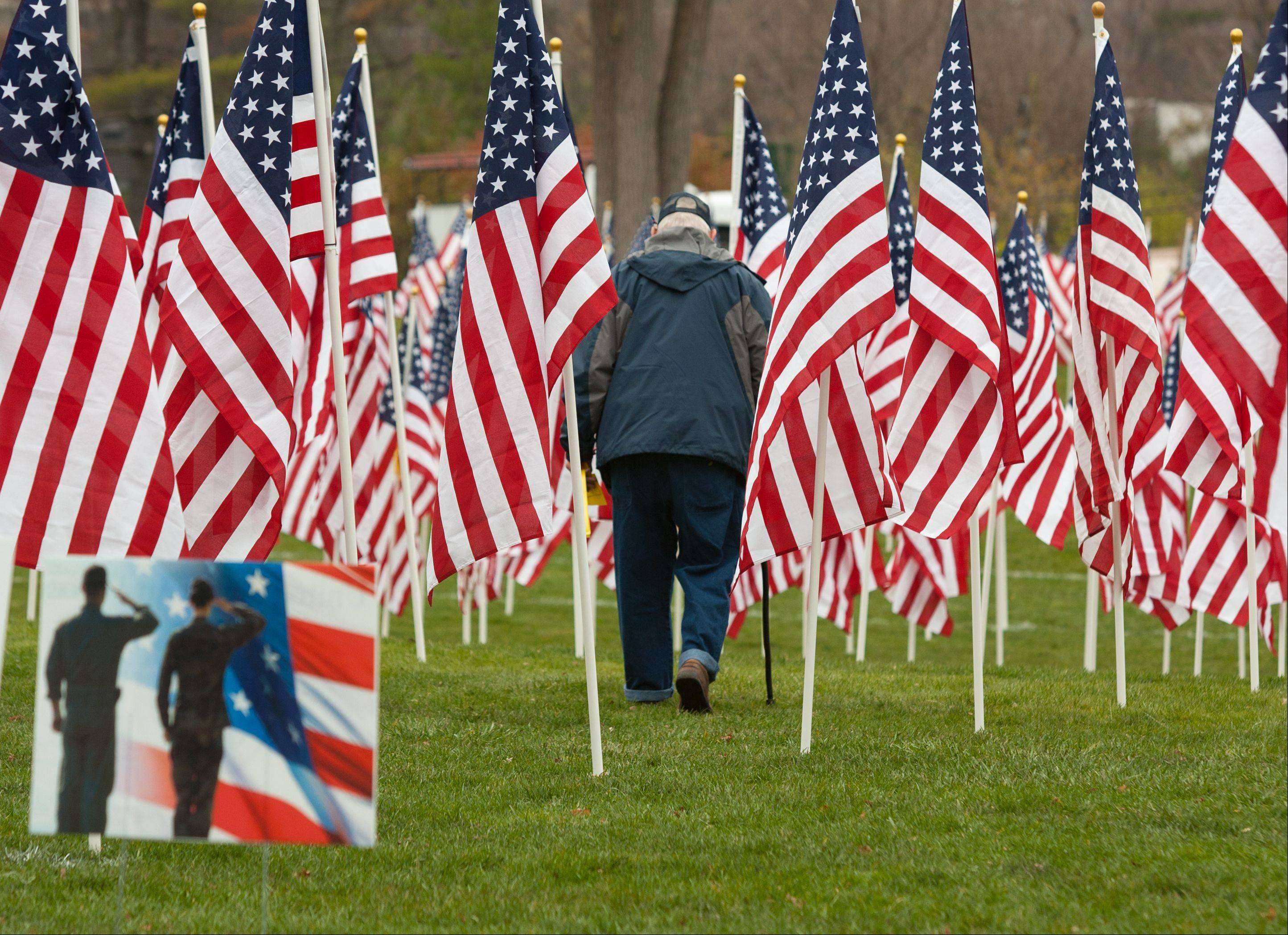 "George Hogrewe of Hinsdale leaves the ""Healing Field of Honor"" tribute to veterans Thursday at Naperville's Rotary Hill. Hogrewe fought in the Pacific aboard the USS Detroit during World War II."