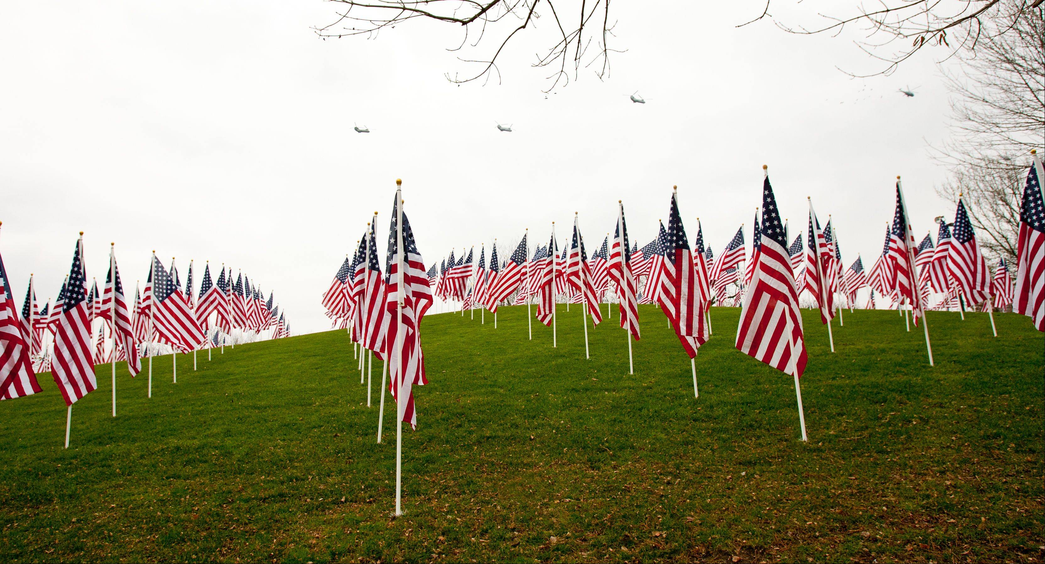 "Helicopters pass over the ""Healing Field of Honor"" on Thursday at Naperville's Rotary Hill, where 2,012 flags are on display in tribute to veterans."