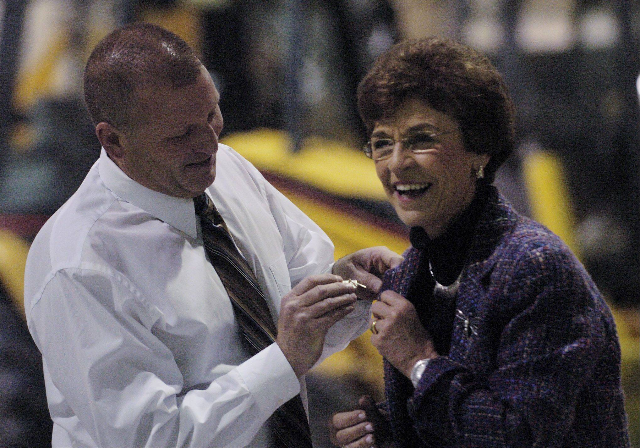 Director of Public Works Scott Shirley pins a broach on the lapel of Arlington Heights Mayor Arlene Mulder.
