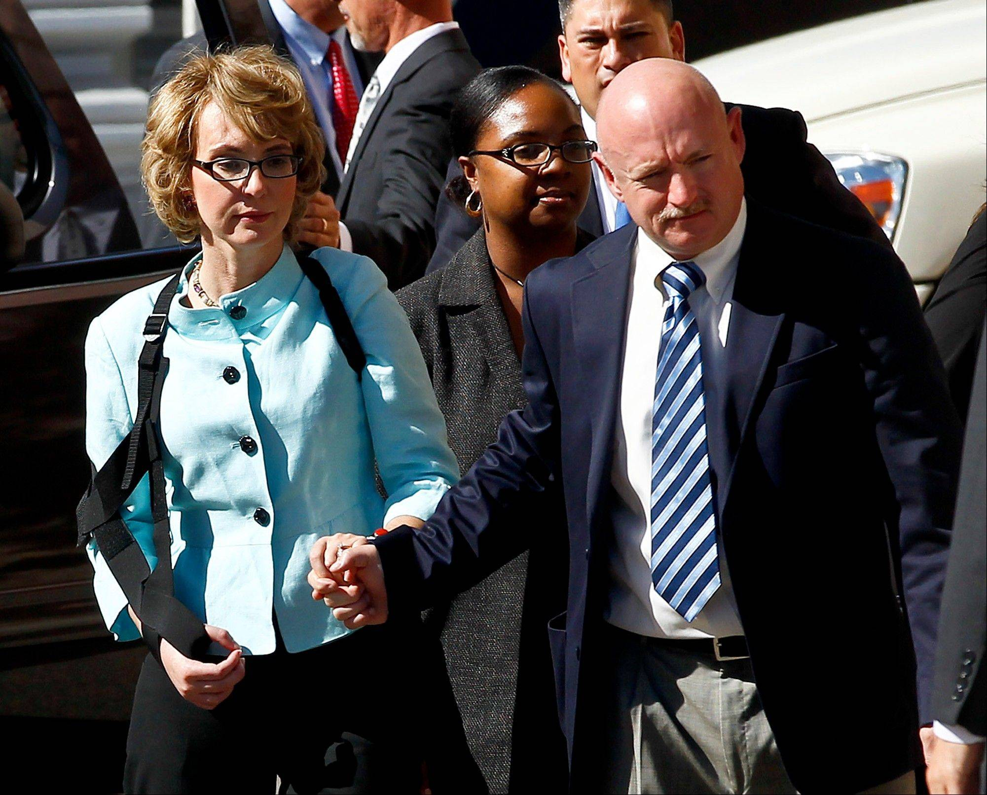 Former Democratic Rep. Gabrielle Giffords, left, and her husband Mark Kelly leave after the sentencing of Jared Loughner on Thursday in Tucson, Ariz.