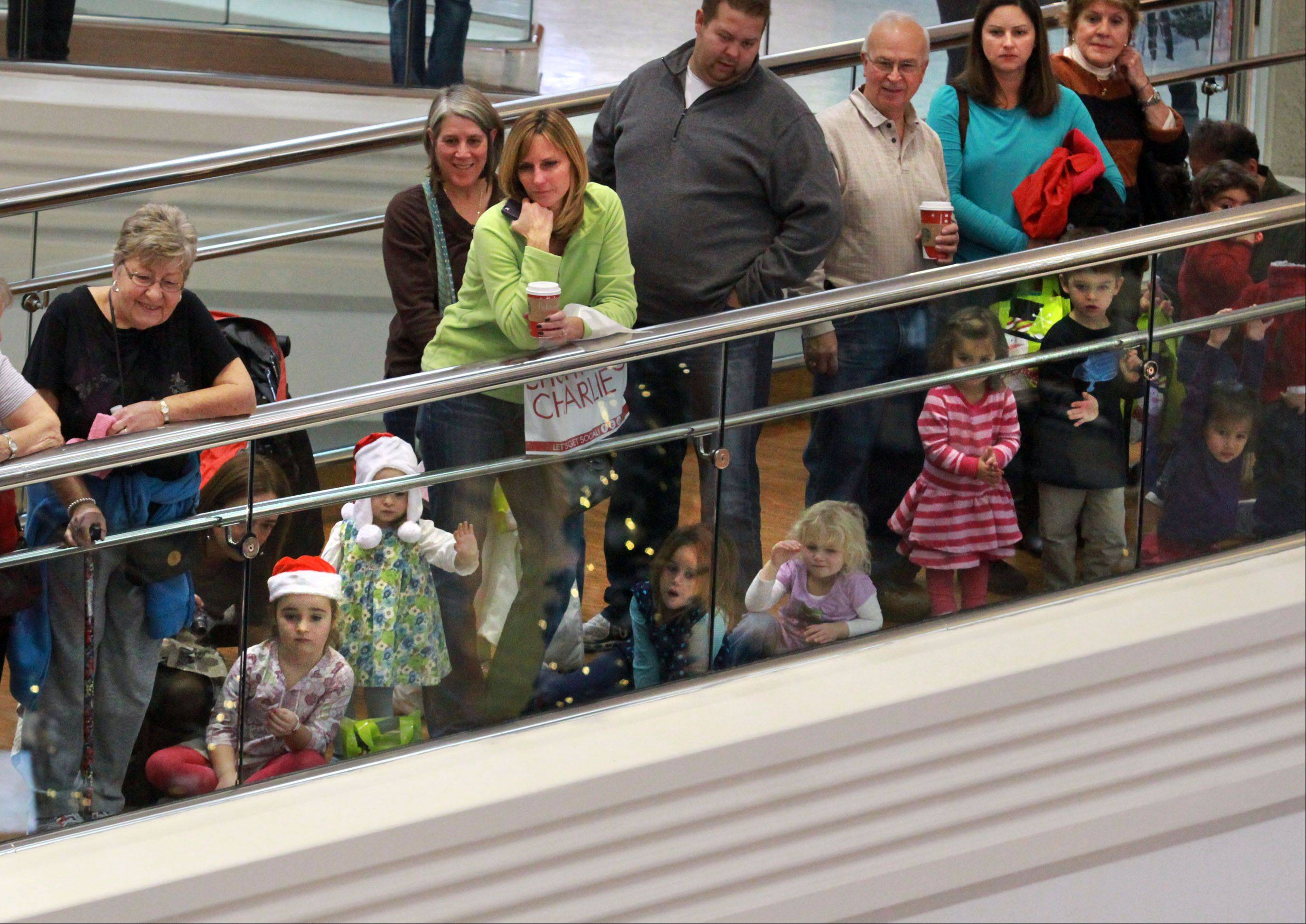 Children and parents watch the Santa Claus parade from the second level of Woodfield Mall in Schaumburg on Thursday. Santa's arrival kicked off the holiday shopping season.