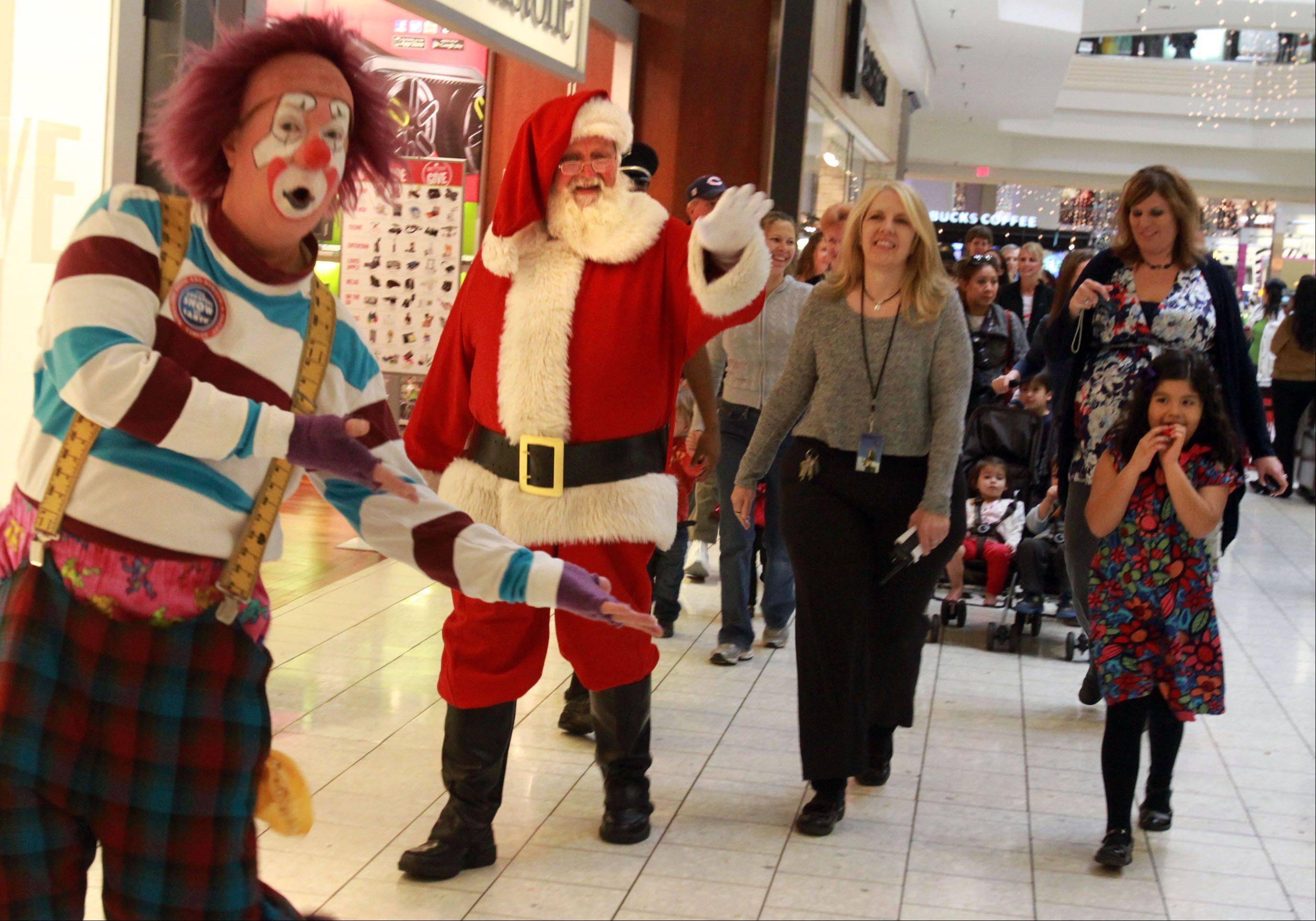 Santa Claus was joined by clowns and a marching band Thursday as he paraded through Woodfield Mall in Schaumburg to kick off the holiday shopping season.