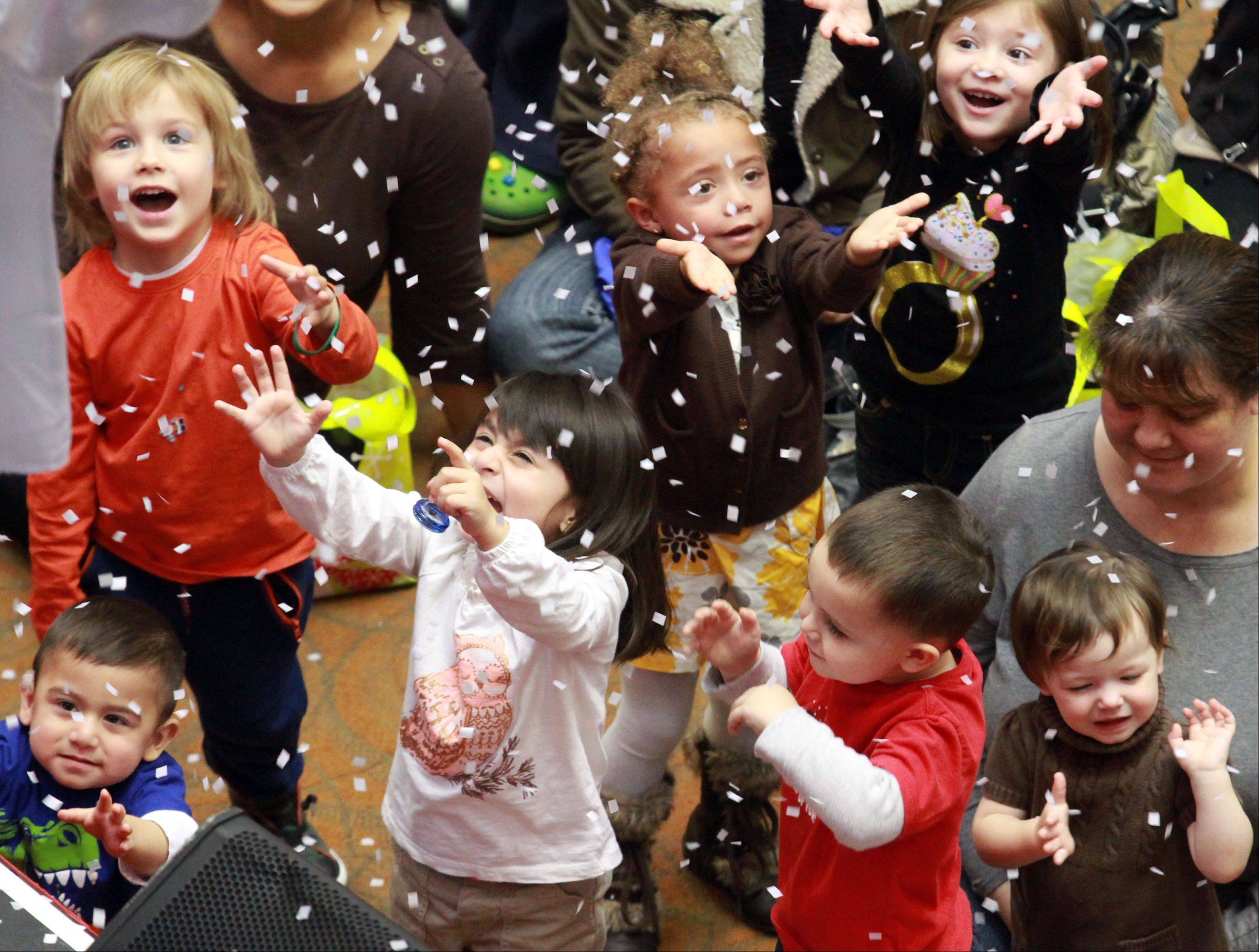 Children try to catch simulated snowflakes during a magic show at the start of the Santa Claus parade at Woodfield Mall in Schaumburg on Thursday.