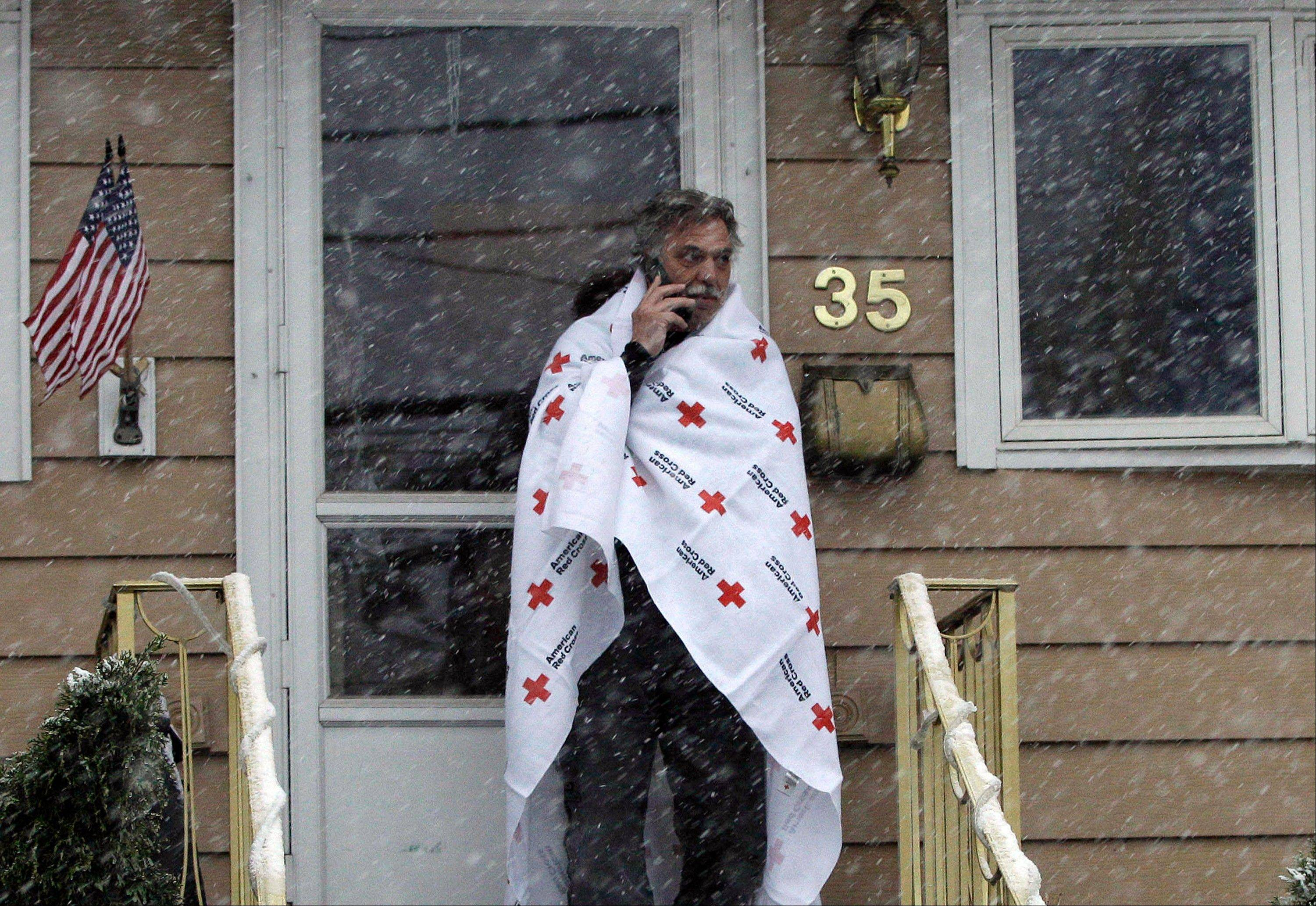 Ben Colontonio talks on his cellphone wrapped in a blanket donated by the American Red Cross as a Nor'easter approaches in the wake of Superstorm Sandy, Wednesday, Nov. 7, 2012, in Little Ferry, N.J.