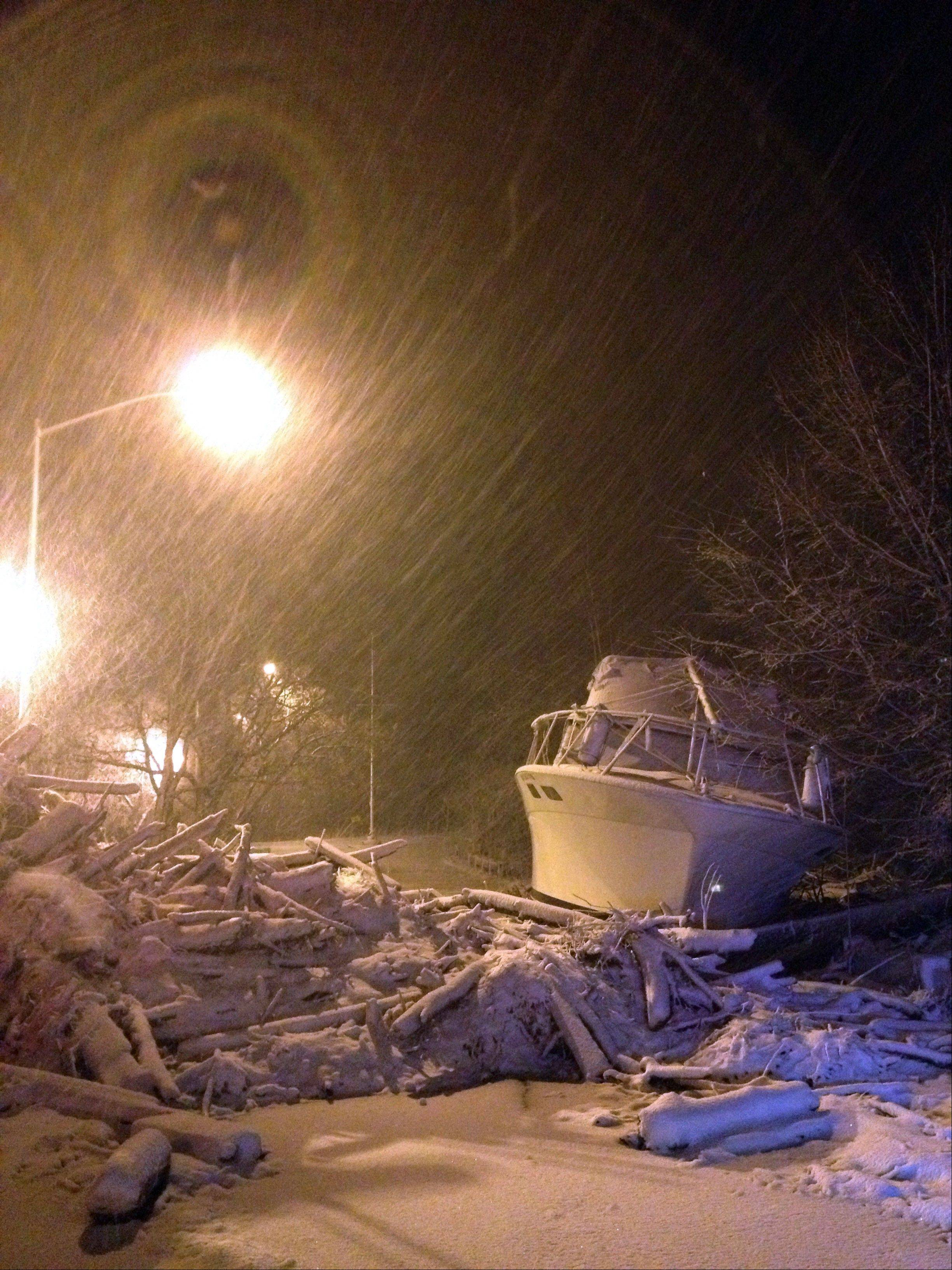 In this photo provided by Tom DeVito, a boat that washed ashore during Superstorm Sandy sits covered in snow on Hylan Blvd. in the Staten Island borough of New York as a nor'easter hits the city, Wednesday, Nov. 7, 2012. A nor'easter blustered into New York and New Jersey on Wednesday with rain and wet snow, plunging homes right back into darkness, stopping commuter trains again and inflicting another round of misery on thousands of people still reeling from Superstorm Sandy's blow more than a week ago.