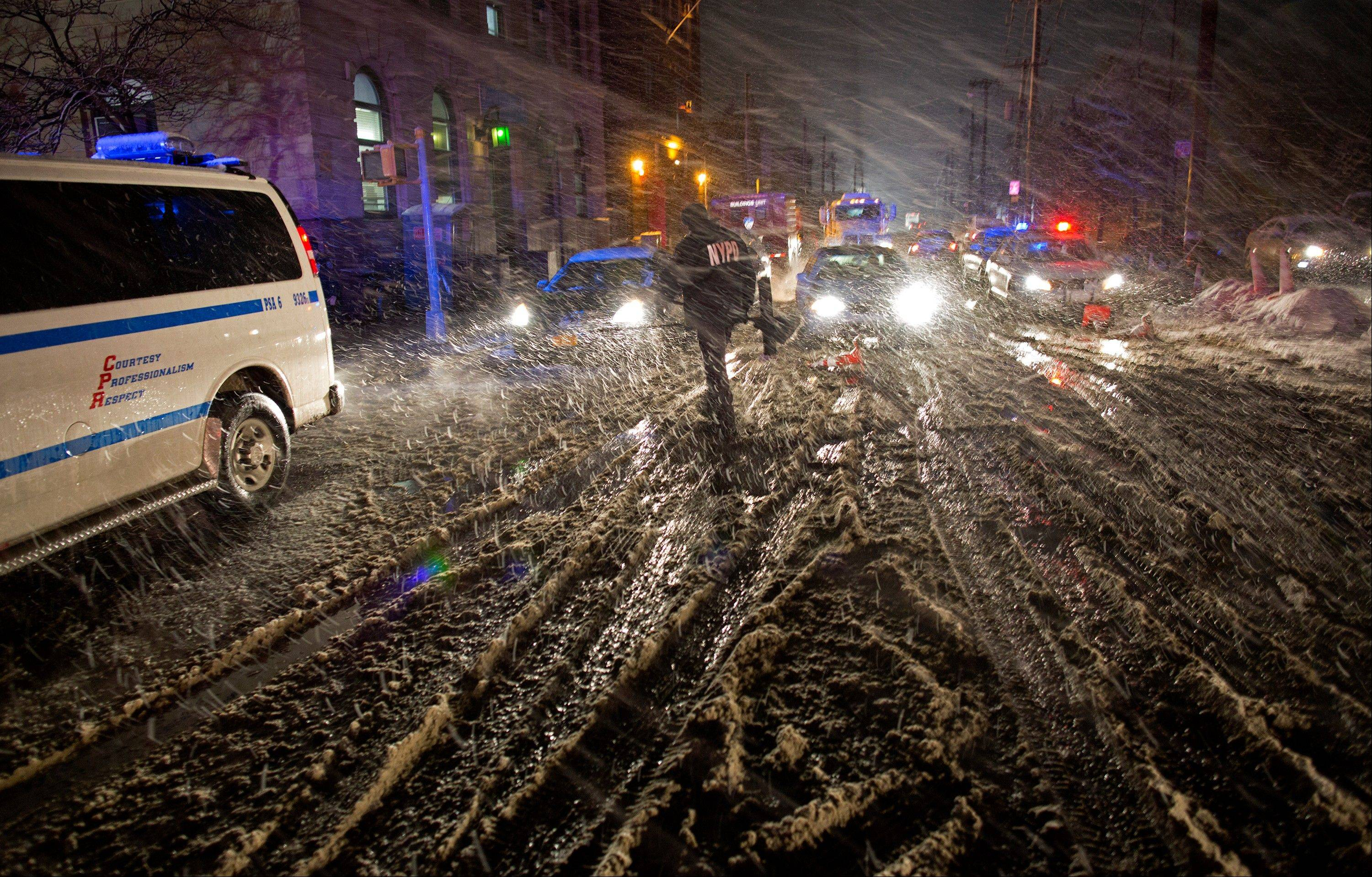 A member of the New York Police Department walks through snow as it accumulates in the Rockaway Beach neighborhood of the borough of Queens, New York, Wednesday, Nov. 7, 2012, in the wake of Superstorm Sandy. A Noreaster is complicating an already difficult situation with wind and blowing snow.
