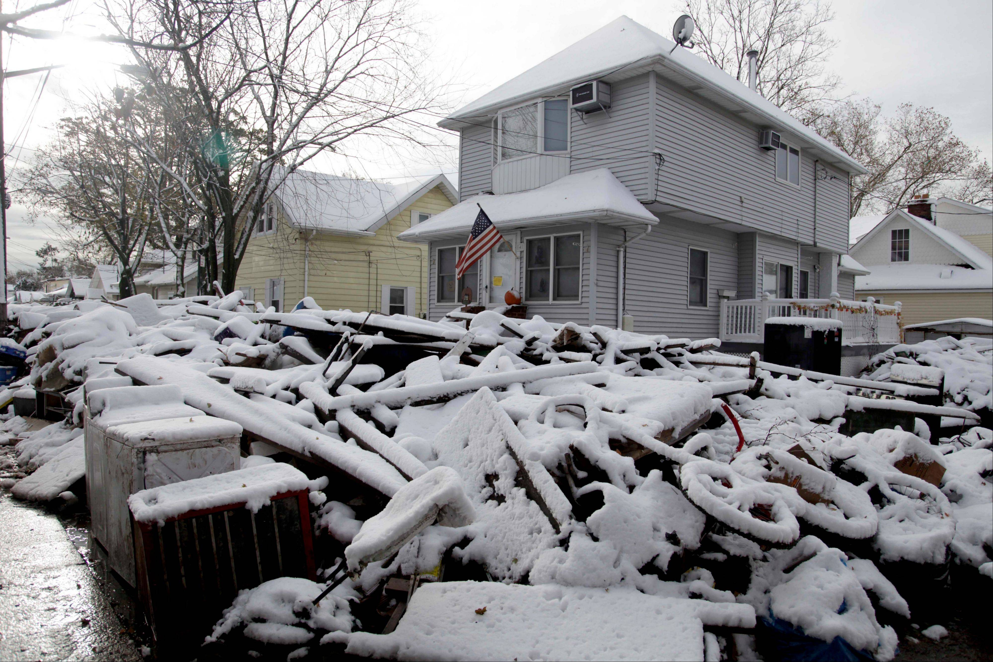 A pile of garbage in the street is covered with snow in the New Dorp section of Staten Island, N.Y., Thursday, Nov. 8, 2012. The New York-New Jersey region woke up to a layer of wet snow and more power outages after a new storm pushed back efforts to recover from Superstorm Sandy.