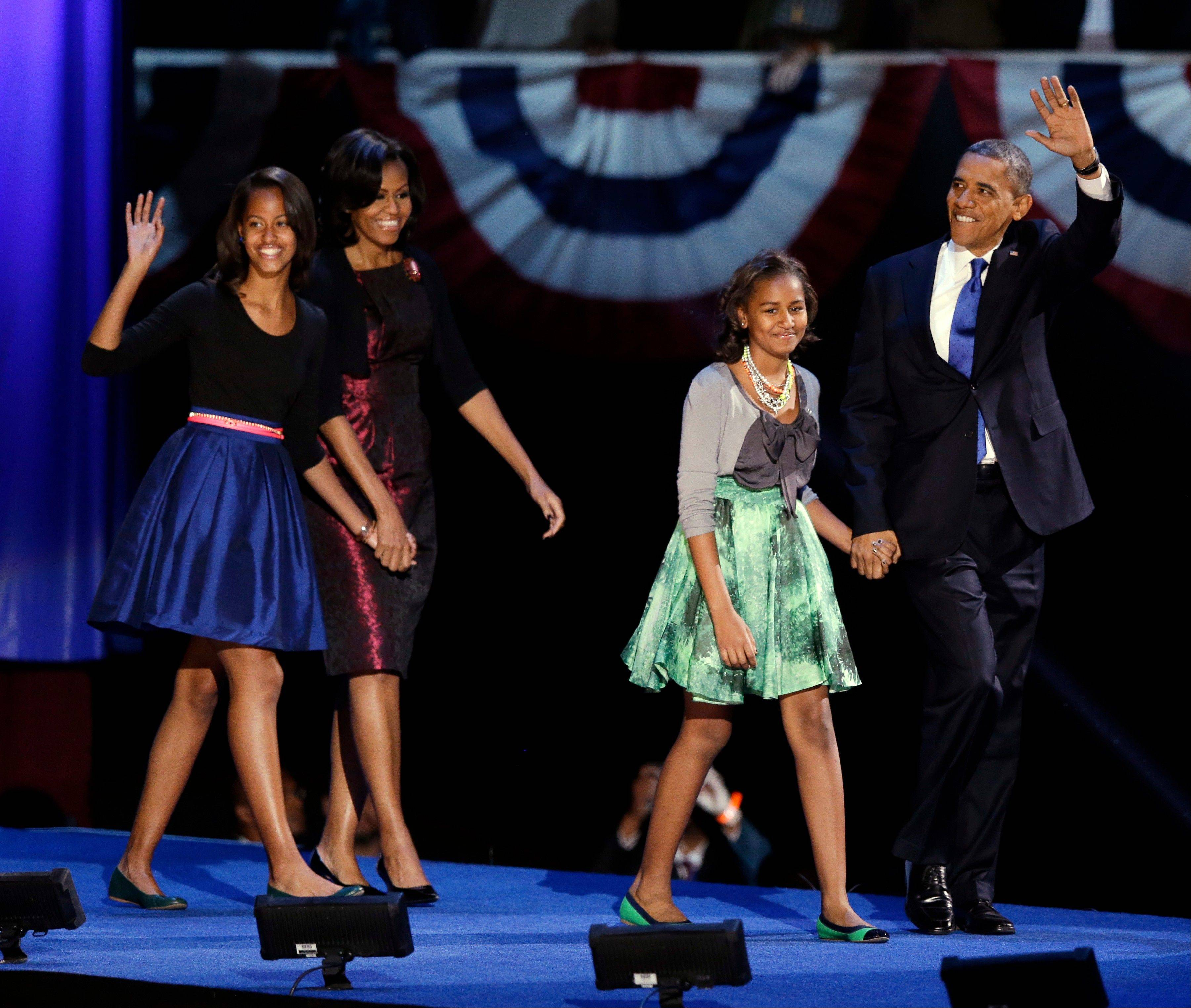 President Barack Obama walks onstage with first lady Michelle Obama and daughters Malia and Sasha at his Election Night party Wednesday in Chicago.