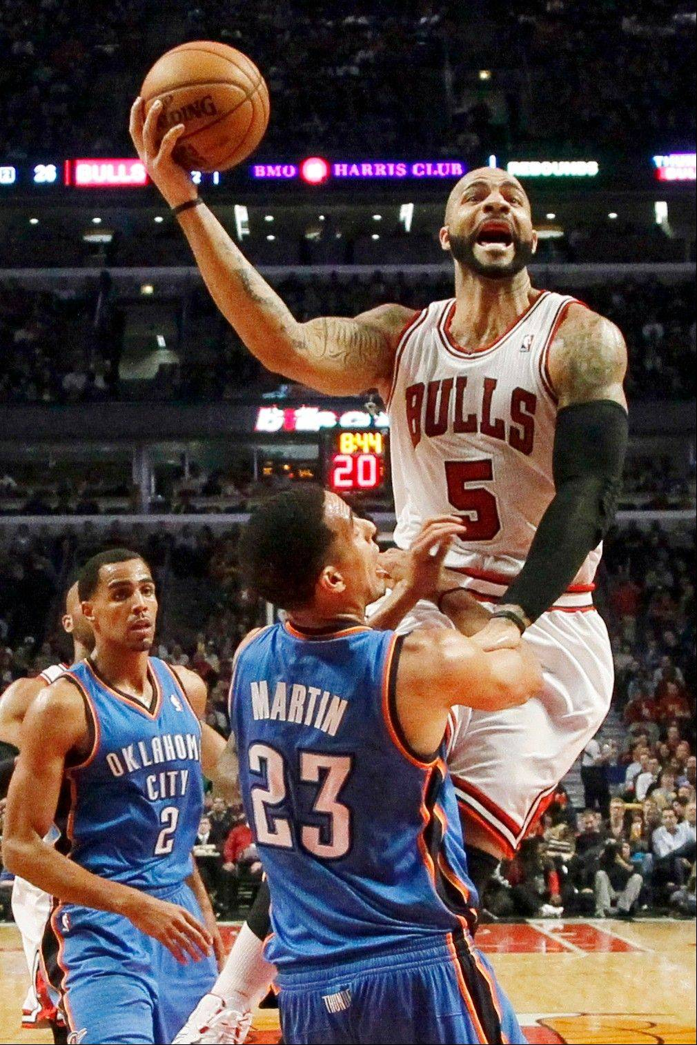 Bulls forward Carlos Boozer shoots over Oklahoma City Thunder guard Kevin Martin (23) as Thabo Sefolosha (2) watches Thursday during the first half at the United Center.