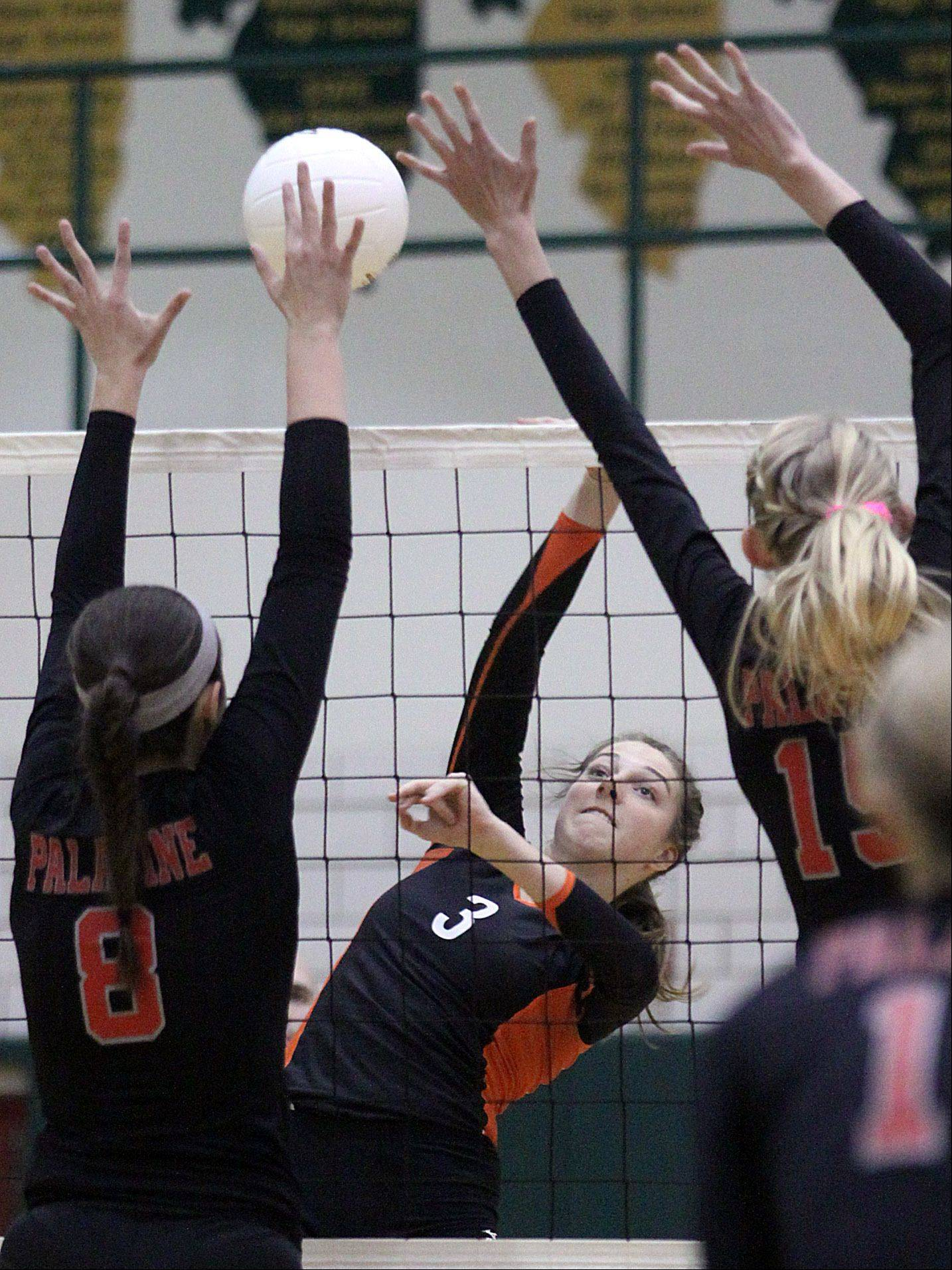 Libertyville's Taylor Zant, center, hits the ball against Palatine during a sectional championship play at Fremd.