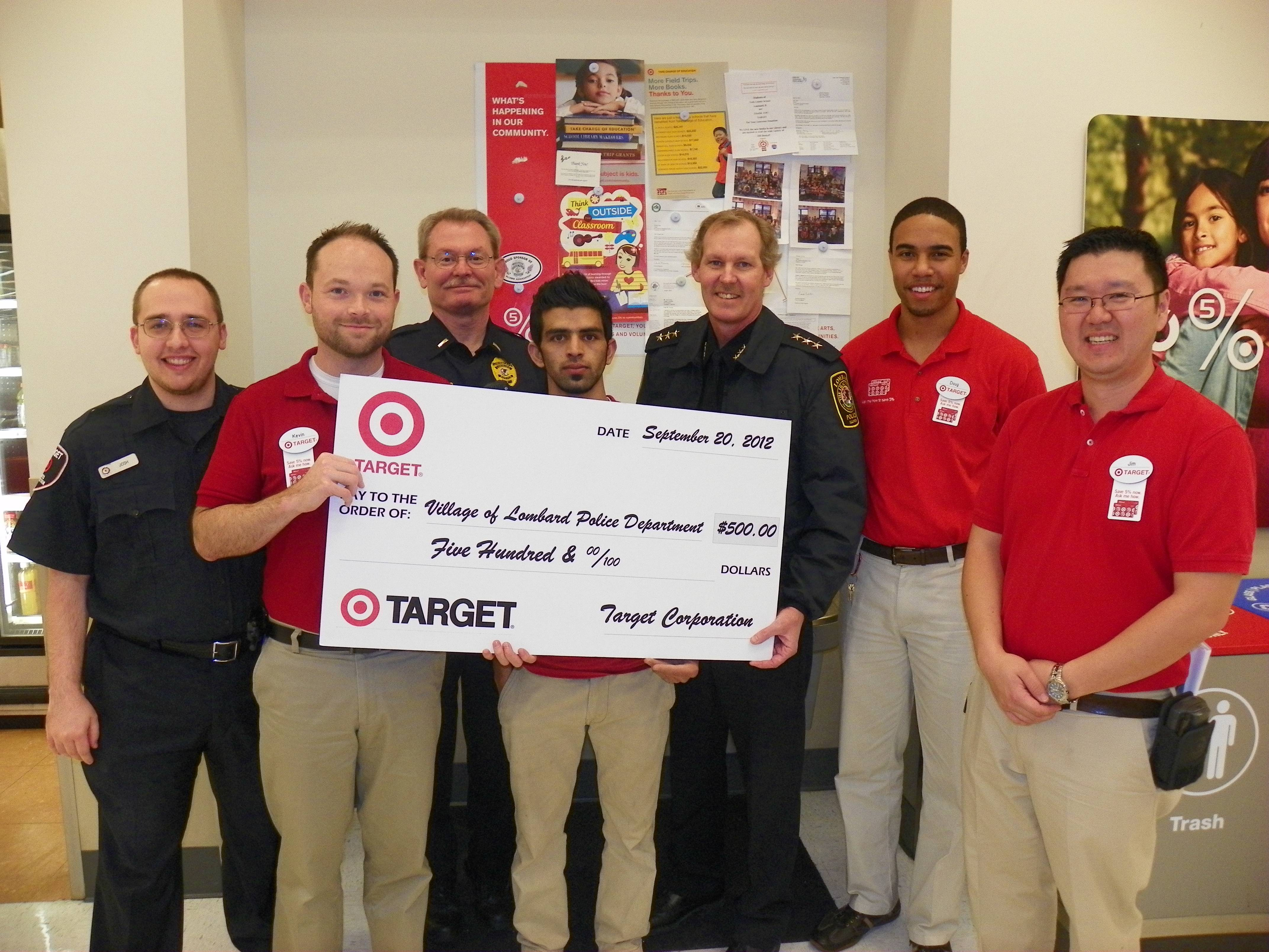Receiving a check for $500 from Target Yorktown Lombard are: (left to right):  Josh Rod and Kevin Mislevy, Target; Lombard Police Lt. Scott Watkins; Zubair Ghiasi, Target; Lombard Police Chief Ray Byrne; Doug Lambert, Target and Jim Kim, Lombard Target Executive Team Leader.