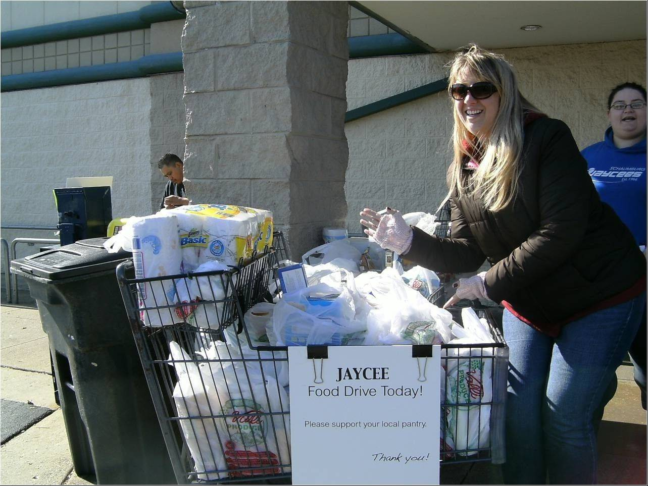 Hoffman Estates Jaycees member Crystal Divis with one of the 10 carts of canned food and nonperishable items collected for the Schaumburg Food Pantry as part of Make A Difference Day.