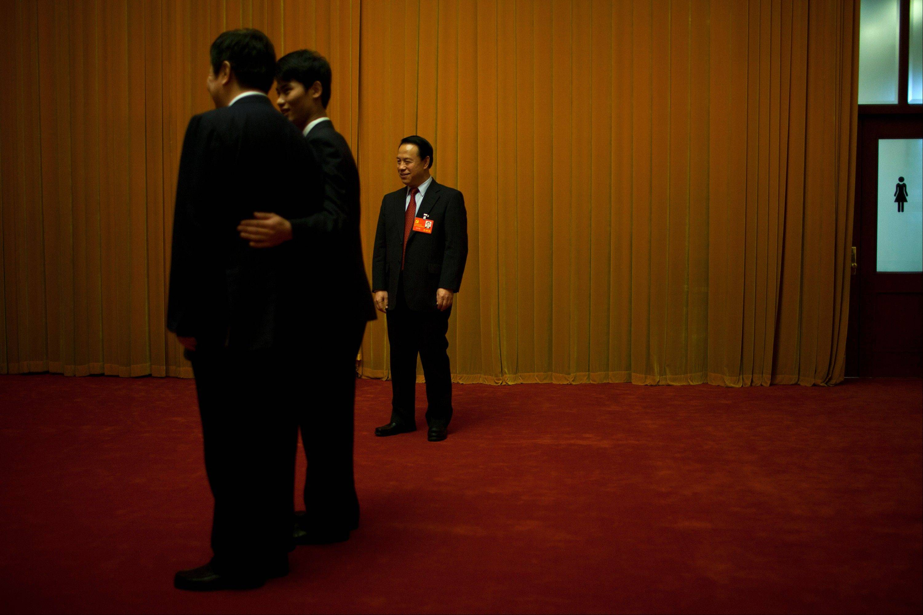 A Communist Party delegate, standing in the background, watches as an usher, front right, puts his arm around another delegate Friday to pose for a photo near a restroom at the Great Hall of the People, where group discussions of the 18th Communist Party Congress is held in Beijing, China.