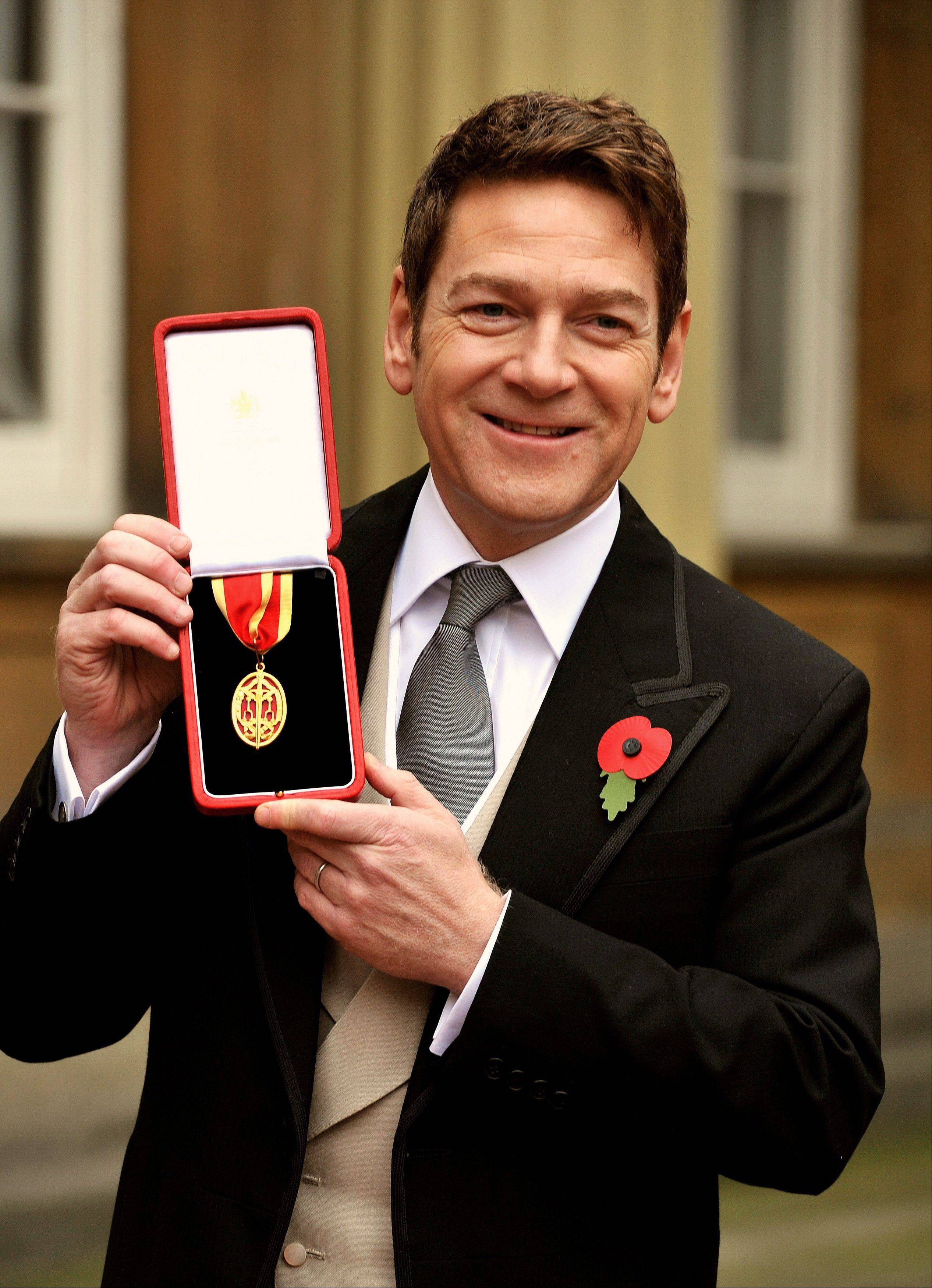 British actor Kenneth Branagh poses with his award after receiving a knighthood from Britain's Queen Elizabeth II at an investiture ceremony at Buckingham Palace in London Friday.