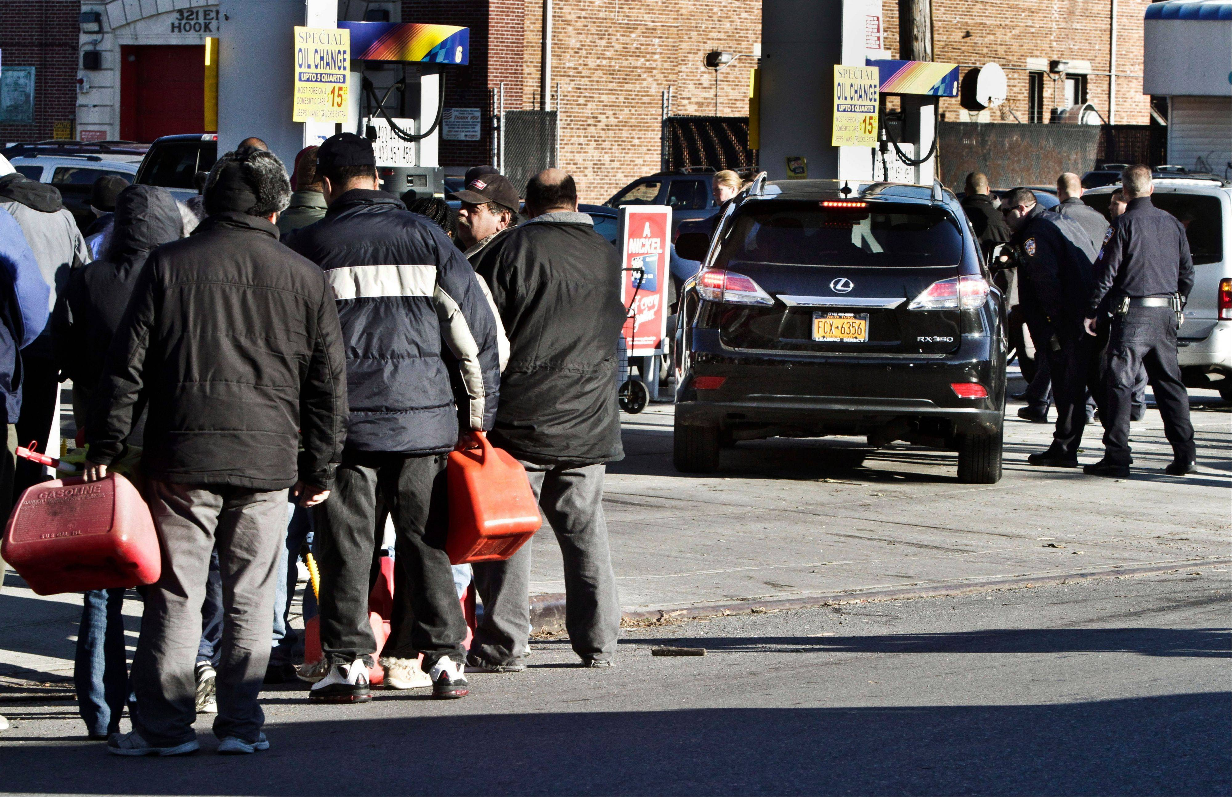 Police direct cars to pumps while people stand in line with containers for gas on Friday, Nov. 9, 2012 in the Brooklyn borough of New York. Police were at gas stations to enforce a new gasoline rationing plan that lets motorists fill up every other day.