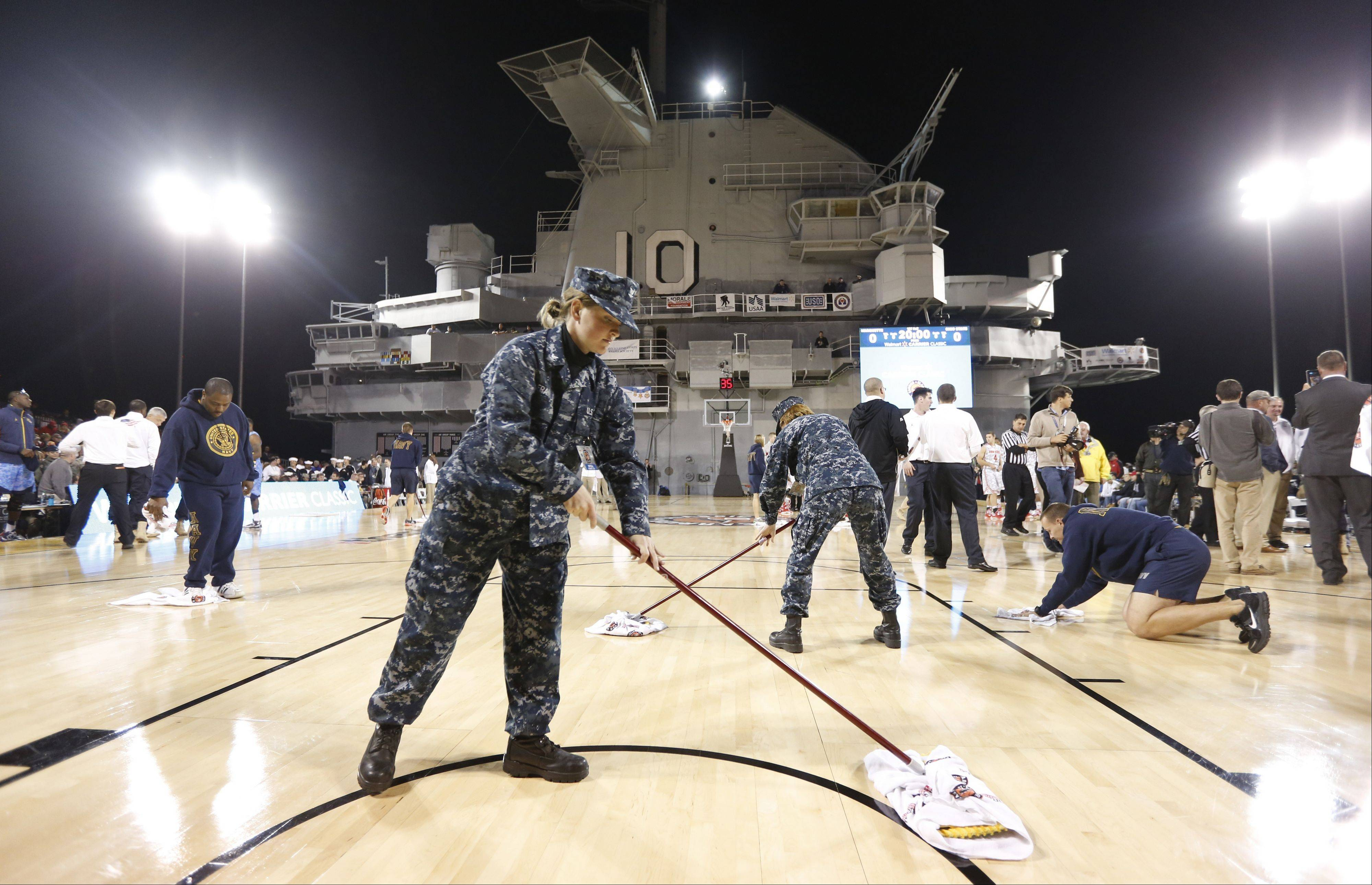 Military personnel and volunteers wipe off condensation in an attempt to dry the damp court Friday before the start of the game between Ohio Sate and Marquette in the Carrier Classic aboard the USS Yorktown in Mount Pleasant, S.C. Officials called off the game because of the damp court.