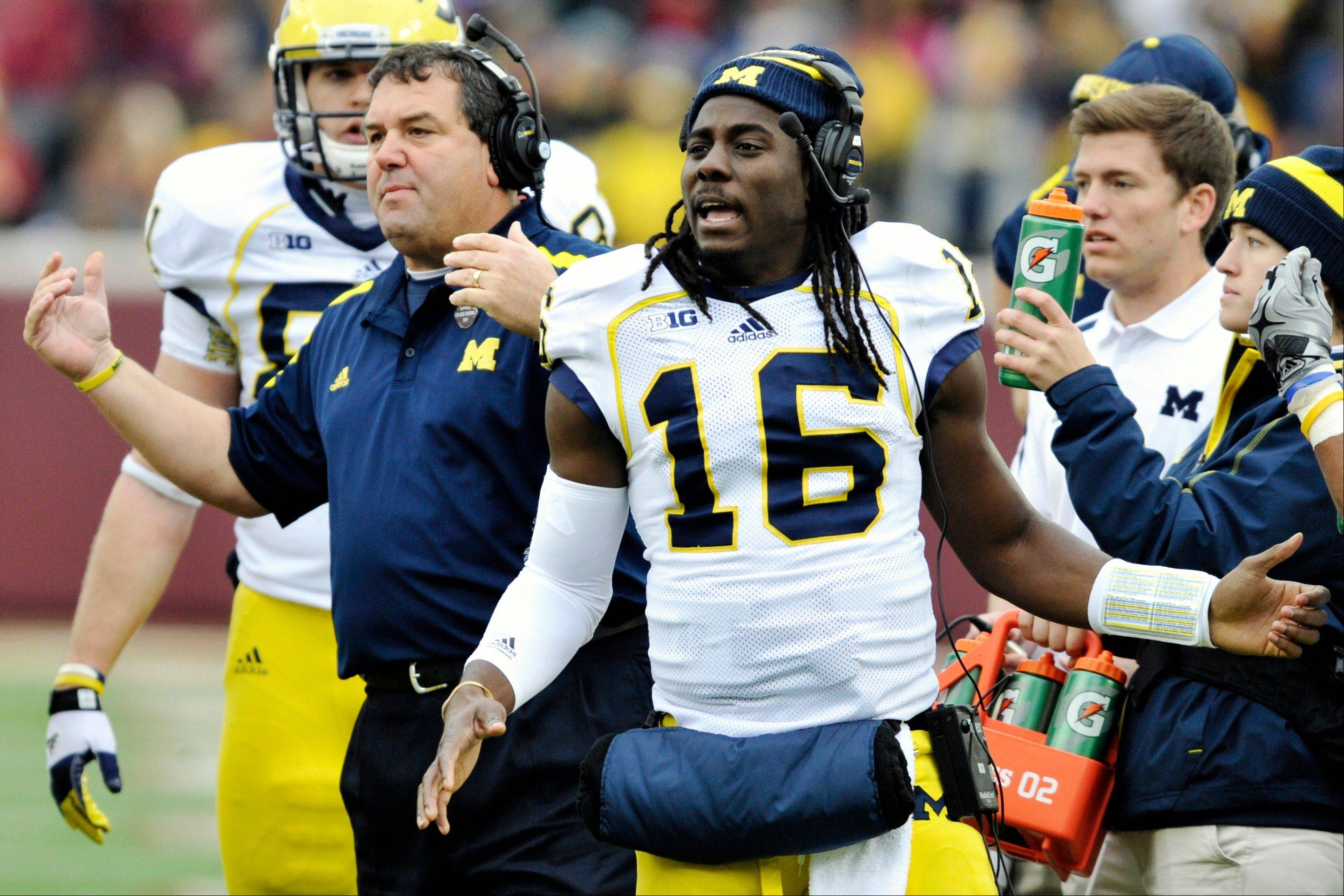 Michigan head coach Brady Hoke, left, and quarterback Denard Robinson, right, call over the offense Saturday during a timeout in the third quarter against Minnesota, Saturday, Nov. 3, 2012, in Minneapolis. Hoke says he's not giving daily updates on Denard Robinson. That leaves everyone — including Northwestern — waiting until Saturday to see if the quarterback is healthy enough to play.