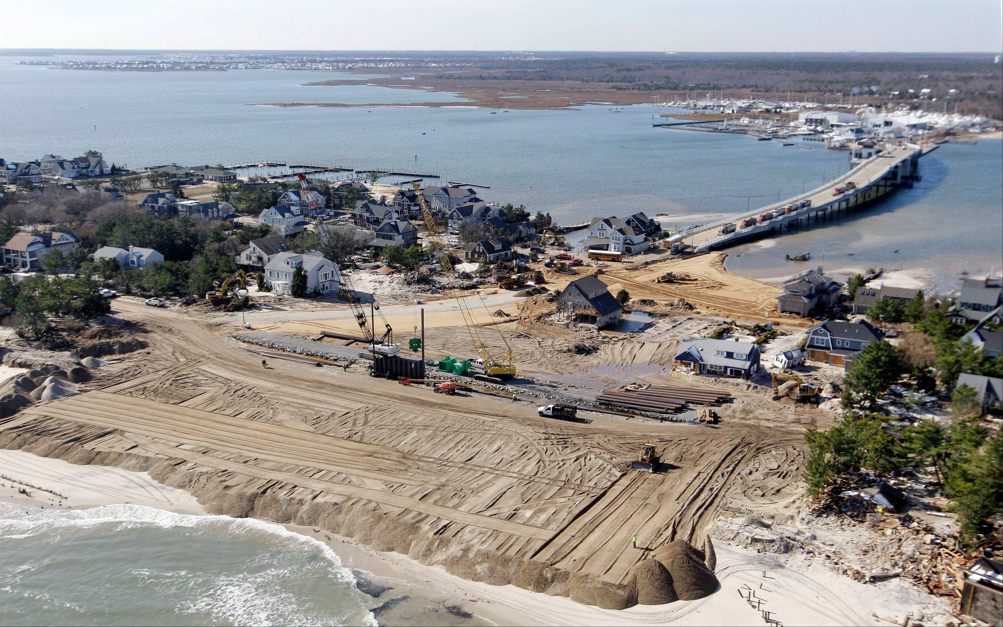 Associated PressIn this aerial photograph, restoration work continues Friday in Mantoloking, N.J. The storm surge from Sandy cut a path through the town from the Atlantic Ocean to the bayside.