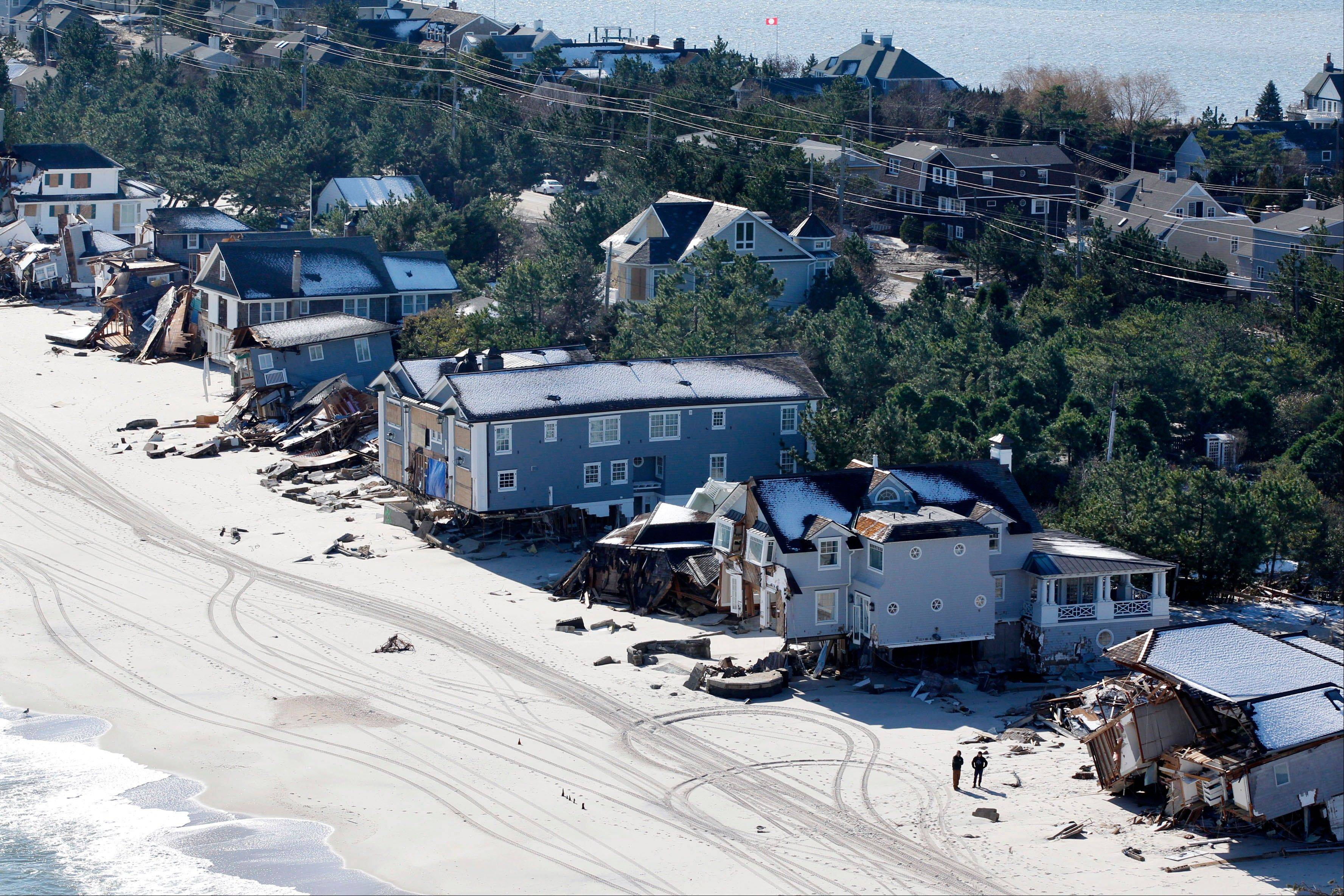 Associated PressIn this aerial photograph, people stand near damaged homes Friday in Mantoloking, N.J.