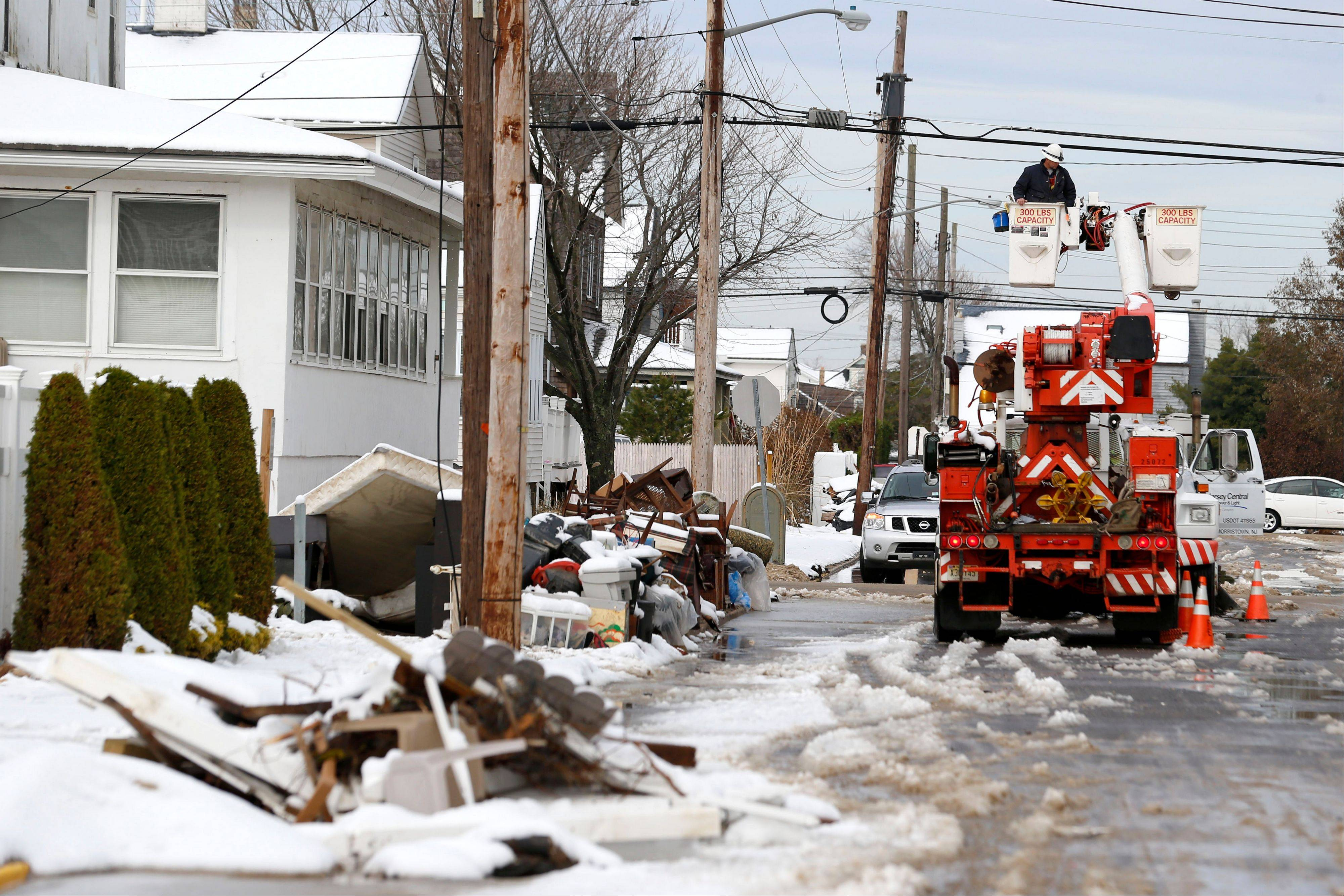 Utility workers check the power lines as snow covered debris from Superstorm Sandy lay on the side of a street following a nor'easter storm, Thursday, in Point Pleasant, N.J. The New York-New Jersey region woke up to wet snow and more power outages Thursday after the nor'easter pushed back efforts to recover from Superstorm Sandy.