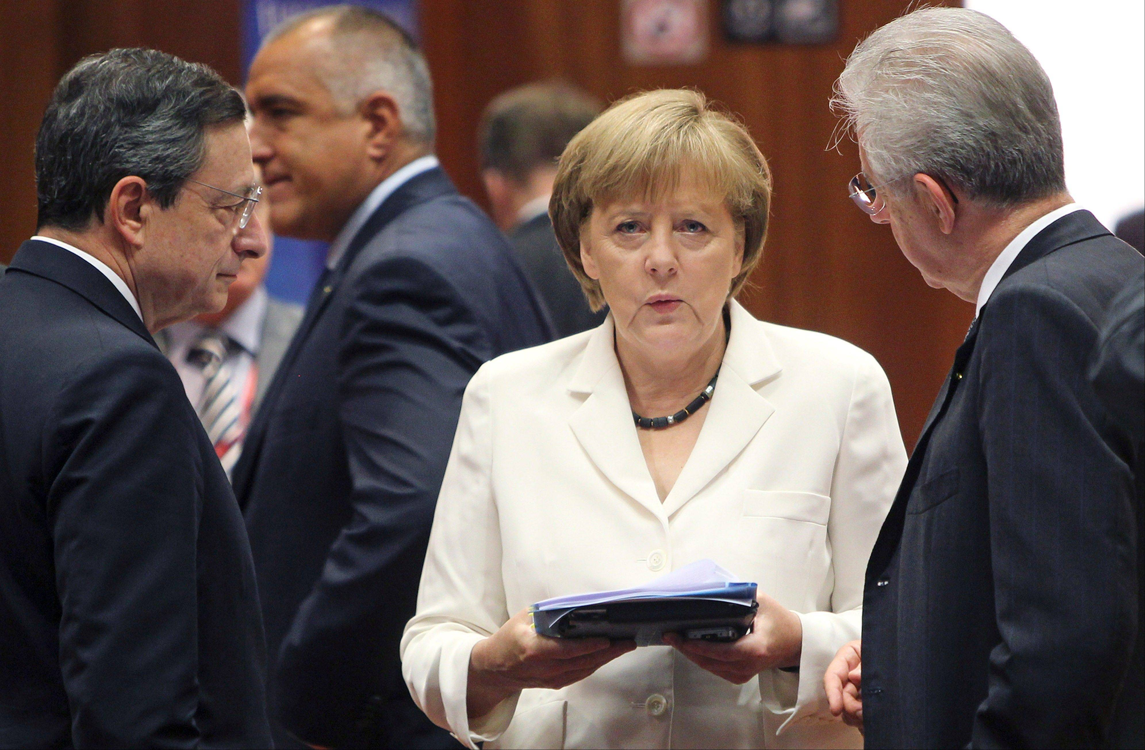 German Chancellor Angela Merkel, center, speaks with European Central Bank President Mario Draghi, left, and Italian Prime Minister Mario Monti during a round table meeting at a EU Summit in Brussels. The worst of Europe's financial crisis appears to be over.