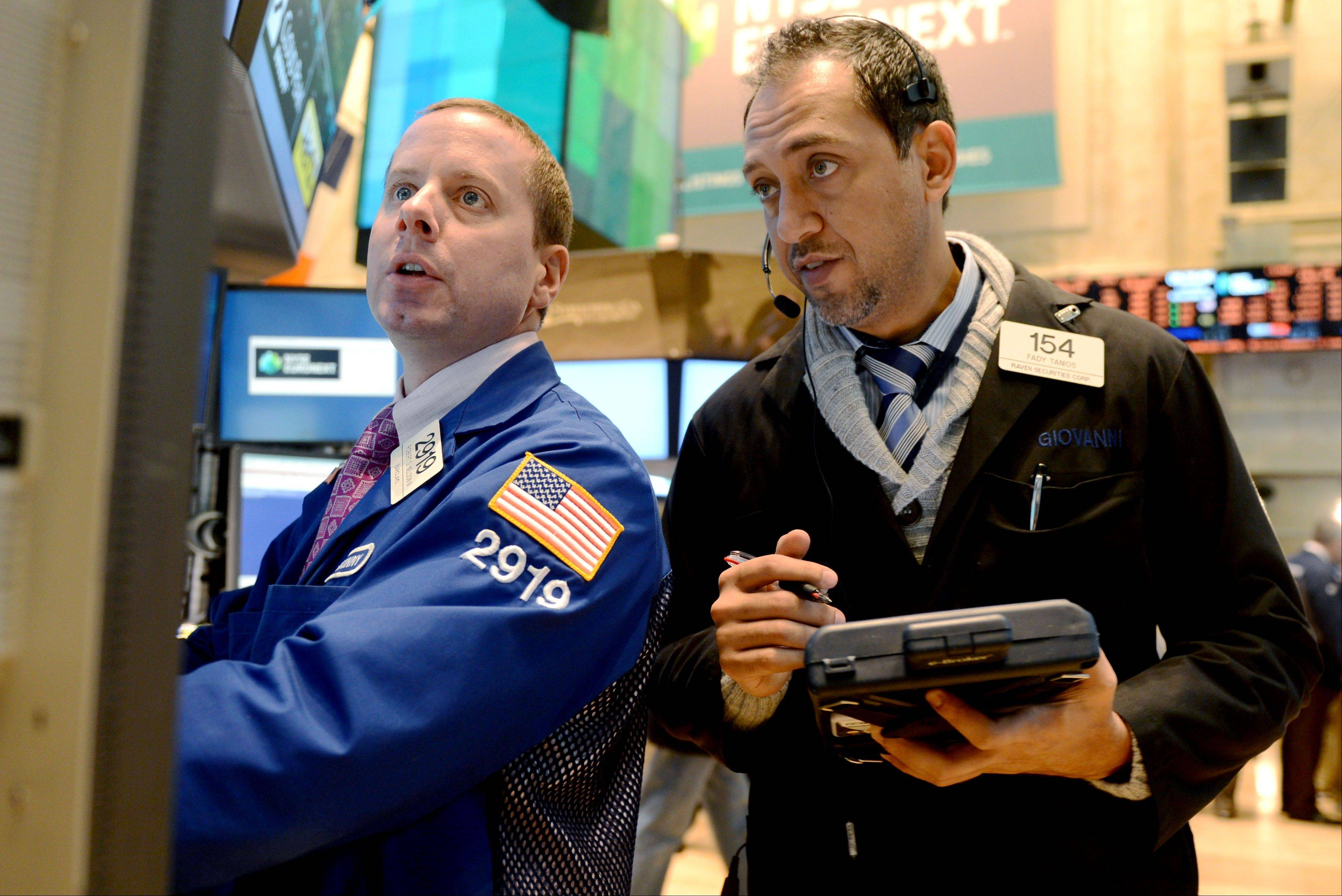 Robert Nelson II of Barclays, left, and Fady Tanios of Raven Securities work on the floor of the New York Stock Exchange, Thursday in New York.