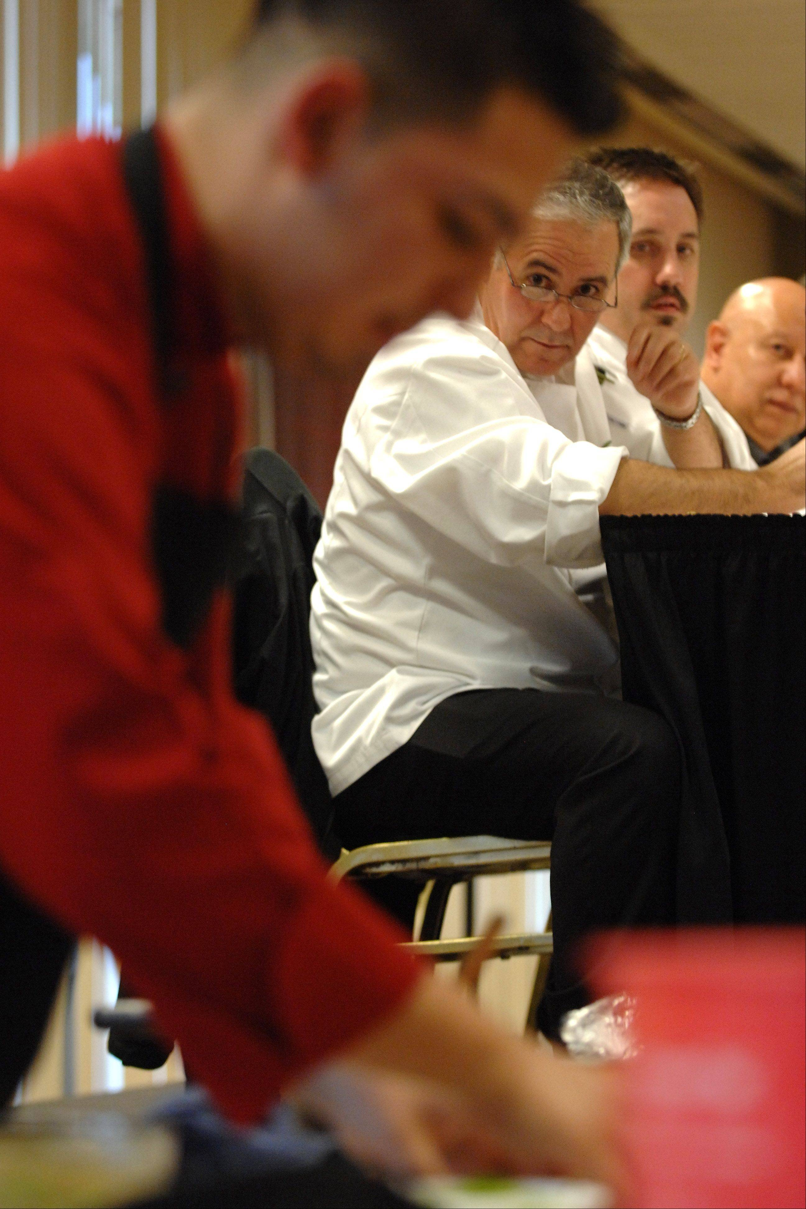 "The judges, including Q Center executive chef Francois Sanchez, watch Juan Ceballos of Elgin work on his ""Pimpin' Supreme Burger"" during the annual Elgin Community College/Prime Burger House burger competition at the Grand Victoria Casino in Elgin Friday."