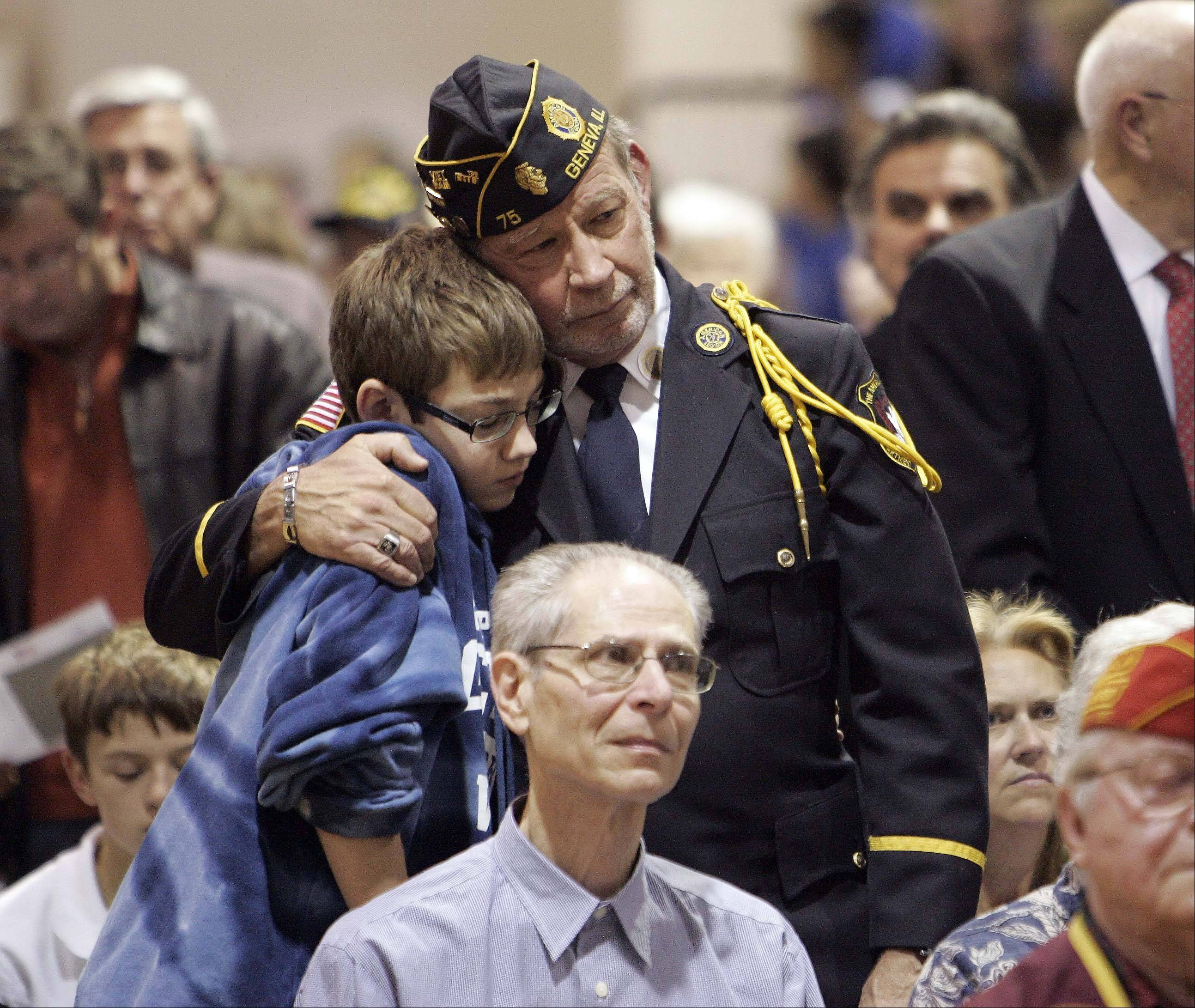 While being honored, Dennis Enneking hugs his thirteen-year-old son Joe, during the Geneva Middle School North annual Veterans Day assembly. Enneking served in Vietnam .