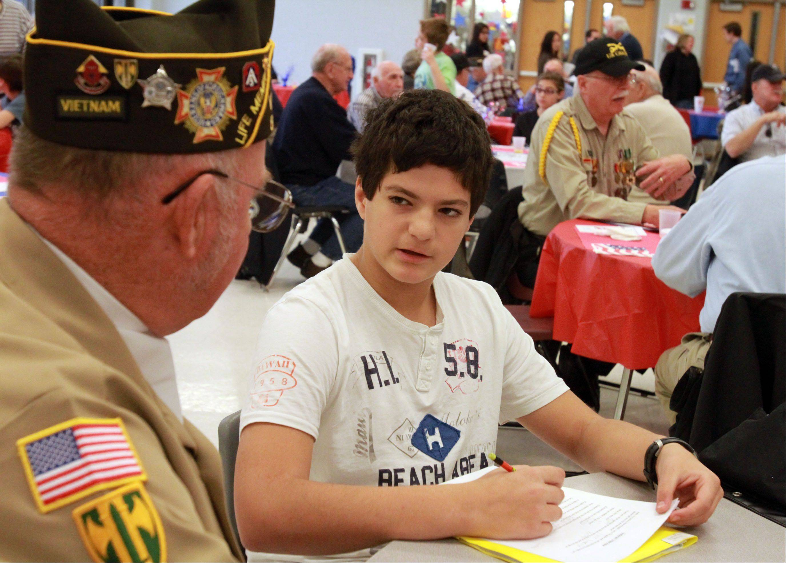 Seventh-grade student Nick Khaytin interviews Tony Kennedy of Libertyville of VFW Post 8741, for his social studies class, after a Veteran's Day breakfast and program at Hawthorn Middle School in Vernon Hills on Friday, November 9, 2012.