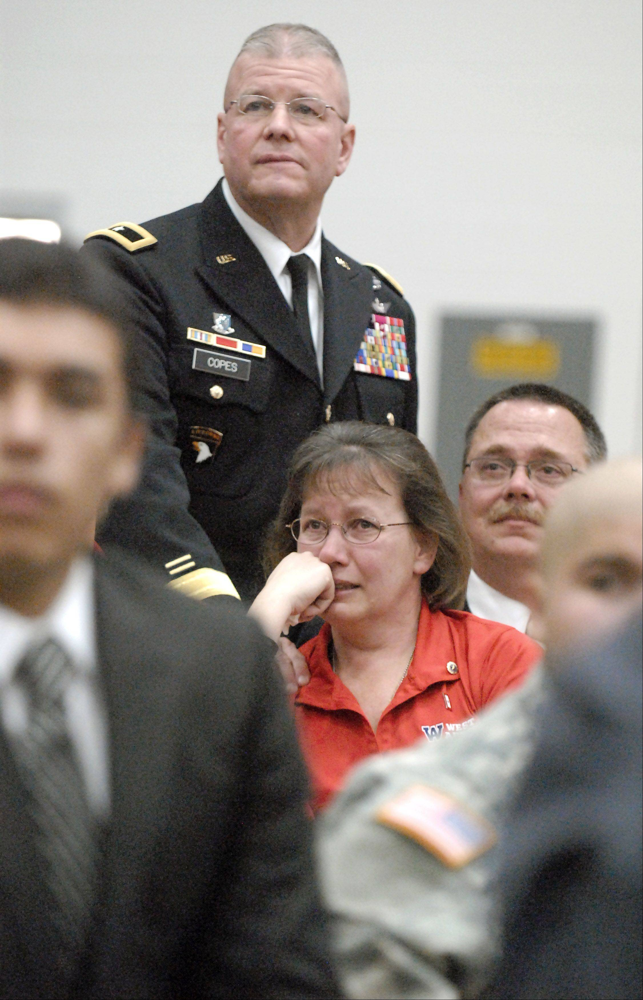 Mary and Bob Patterson are comforted by Brigadier General Brian Copes, Joint Chief of Staff with the Indiana National Guard, as they watch a video tribute to their late son and West Aurora High School alumni, SPC Christopher Alexander Patterson, at West Aurora High School's Veterans Day celebration on Friday, November 9. Patterson was killed on January 6.