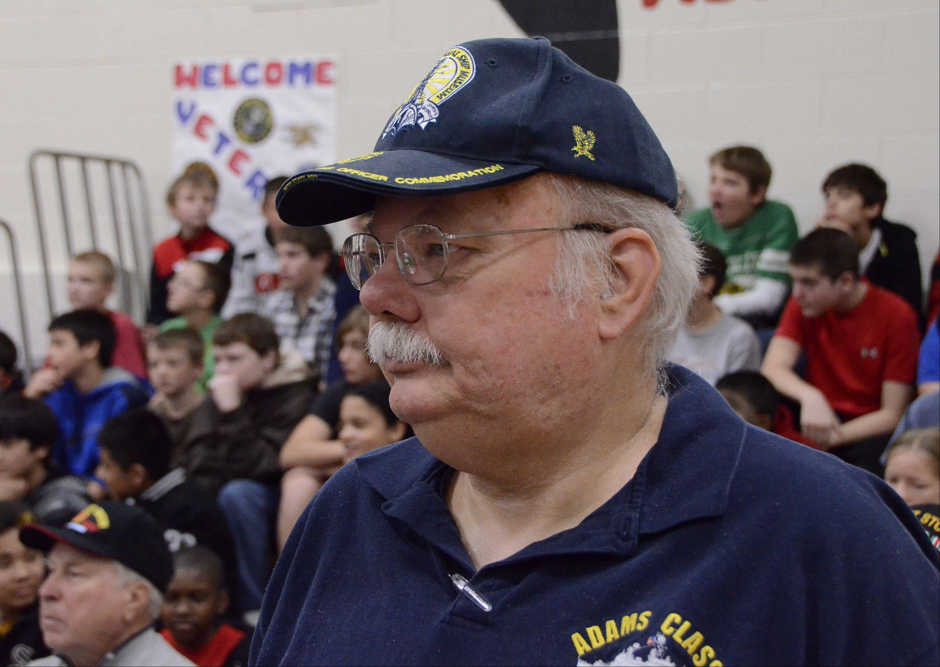 Art Ellingser of Arlington Heights, a Navy veteran of both the Korean and Vietnam Wars, stands while Anchors Aweigh is played at the Veterans Day assembly Friday at MacArthur Middle School in Prospect Heights.