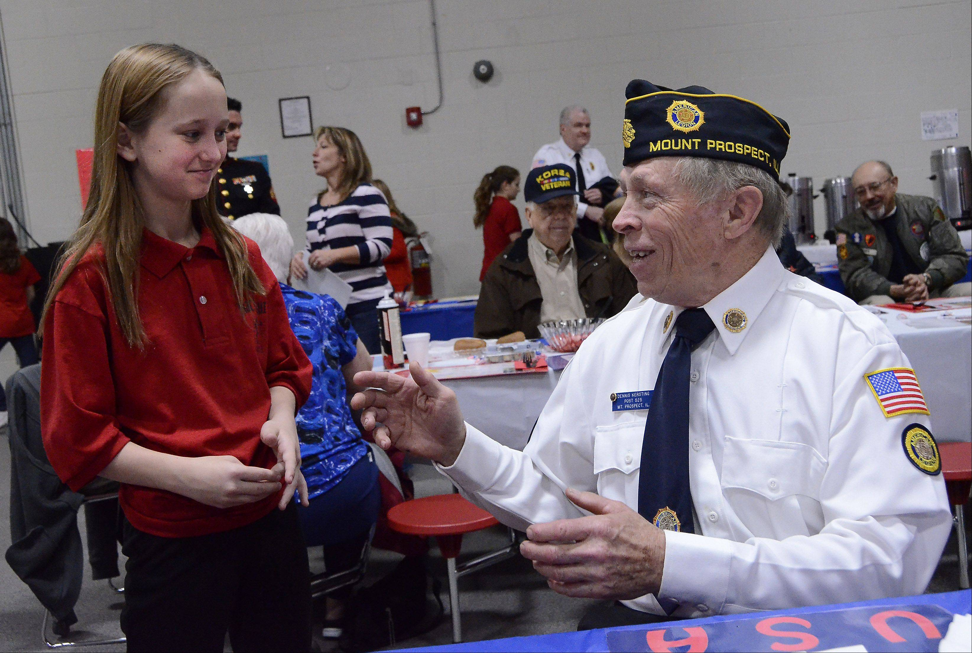 Seventh grade student Nicole Guest of Arlington Heights talks with Dennis Kersting of Des Plaines a veteran who served on the U.S.S. Rigel during the Vietnam War.