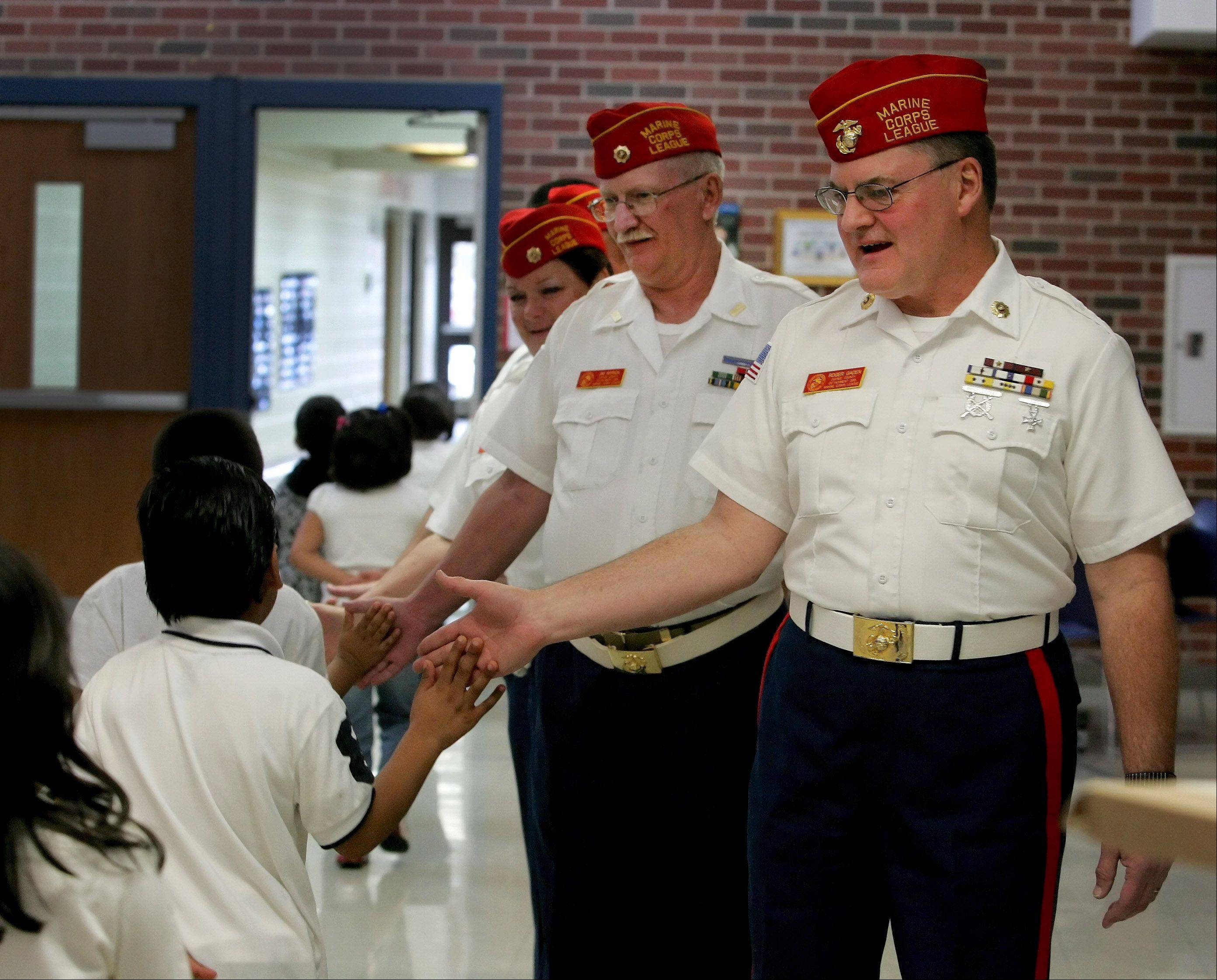 Jim Myrick, left, and Roger Gaden, members of the DuPage County Marines, Detachment 399, greet students as they head in for a Veterans Day program at Johnson Elementary School in Warrenville.