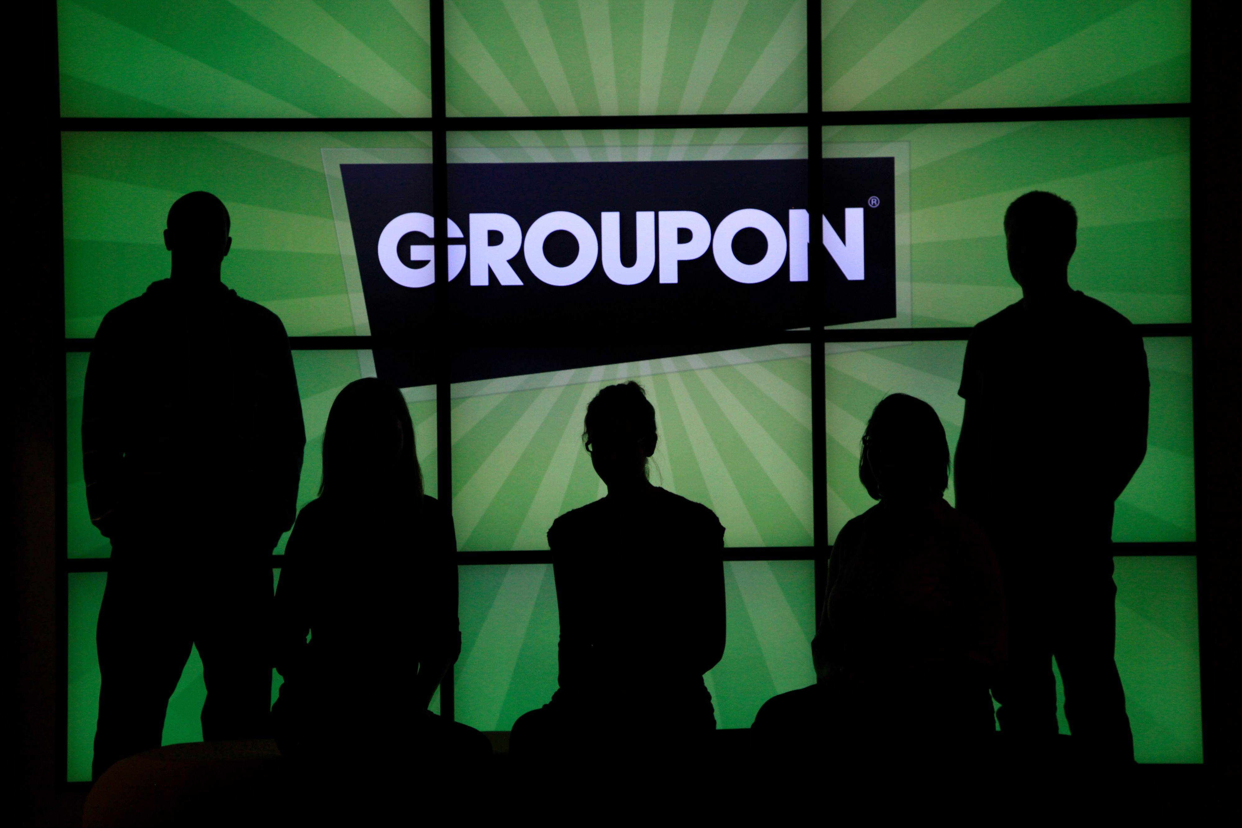 Associated Press/2011Employees at Groupon pose in silhouette by the company logo in the lobby of the online coupon company's Chicago offices.