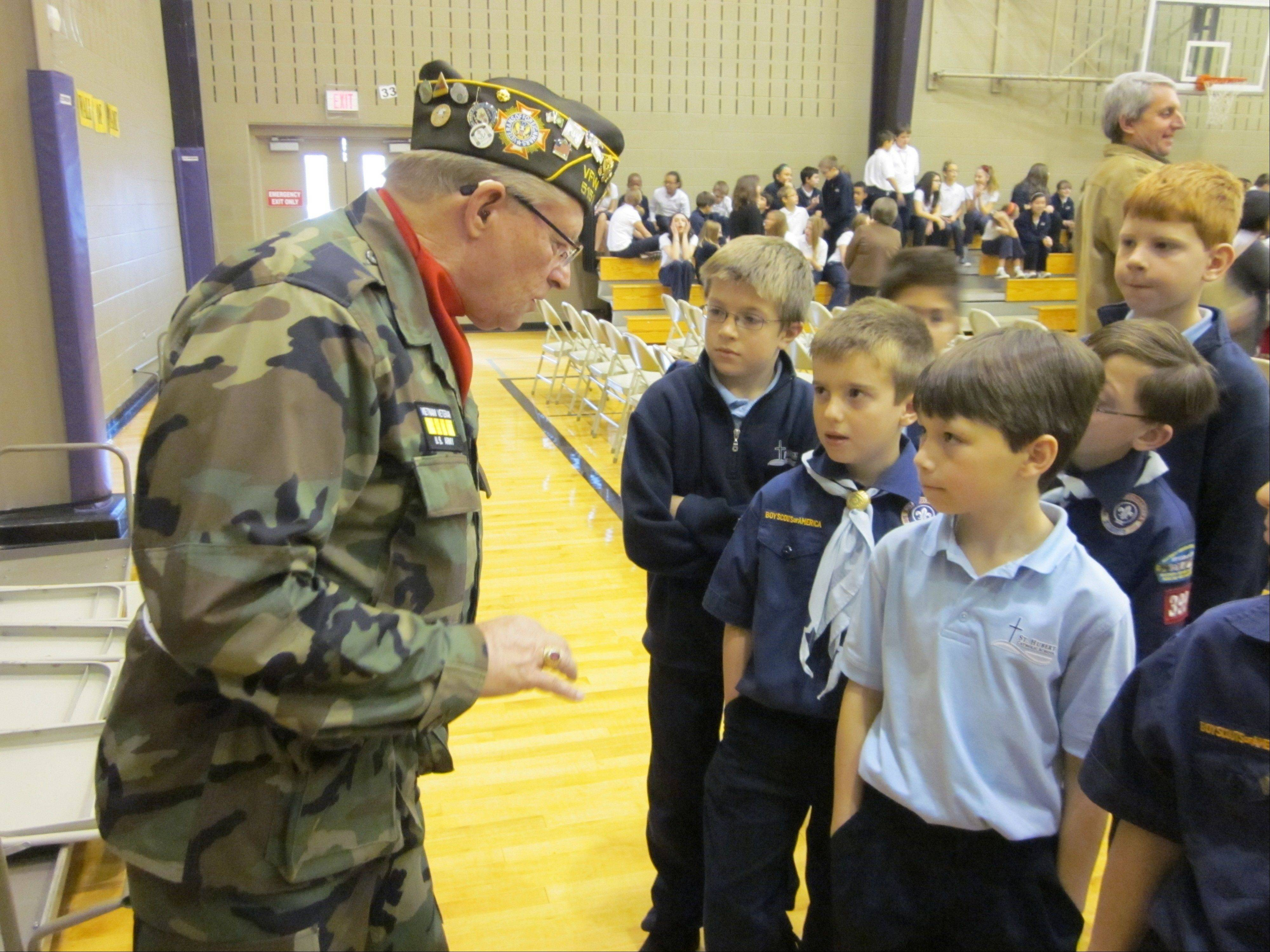 U.S. Army veteran Phil Jelen, who served during the Vietnam War and is now a service officer for VFW Post 5151, talks to students at Saint Hubert Catholic School in Hoffman Estates during a Veterans Day ceremony Friday.