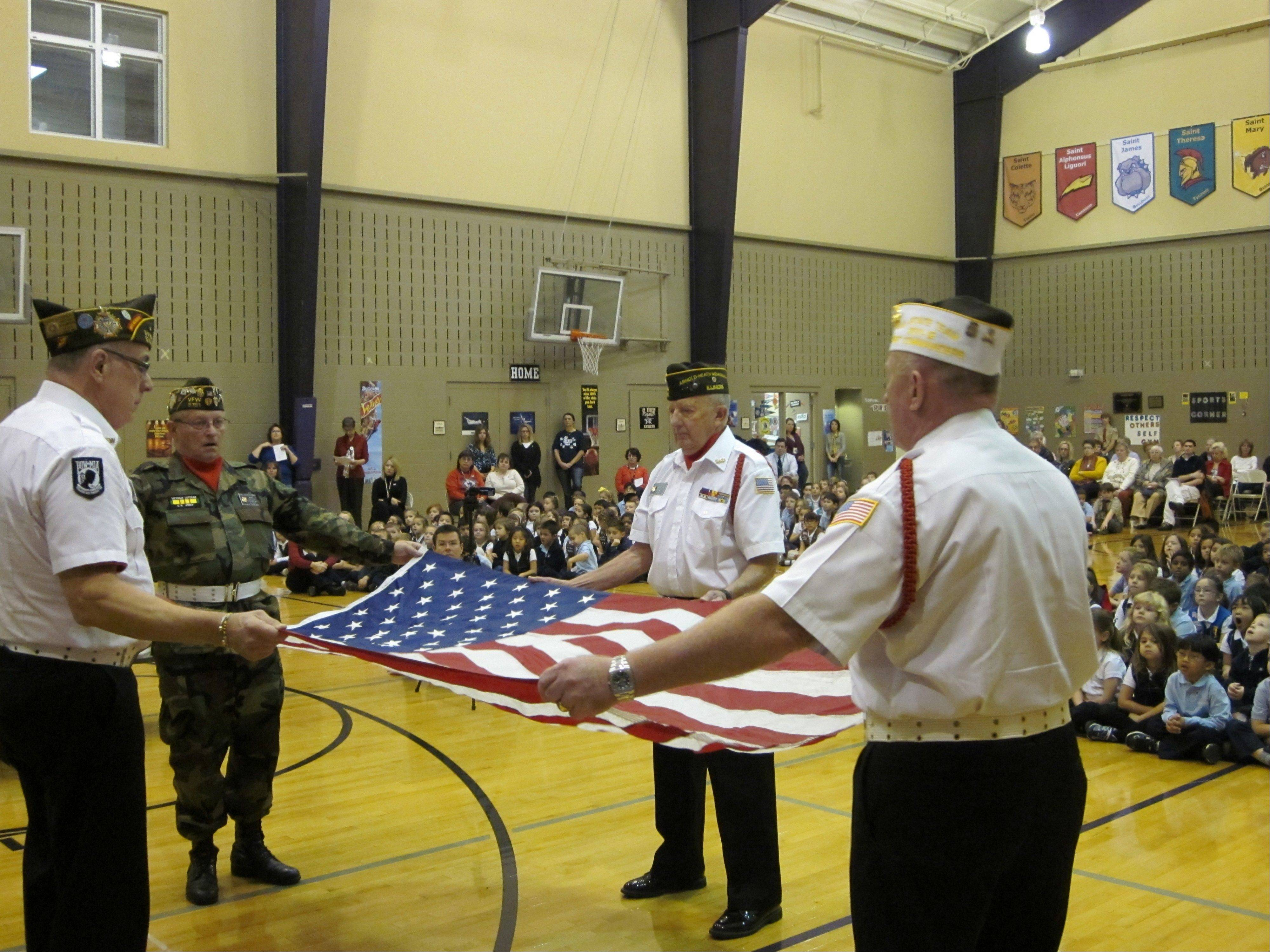 Members of VFW Post 5151 demonstrate the folding of the American flag during a Veterans Day ceremony Friday at Saint Hubert Catholic School in Hoffman Estates.